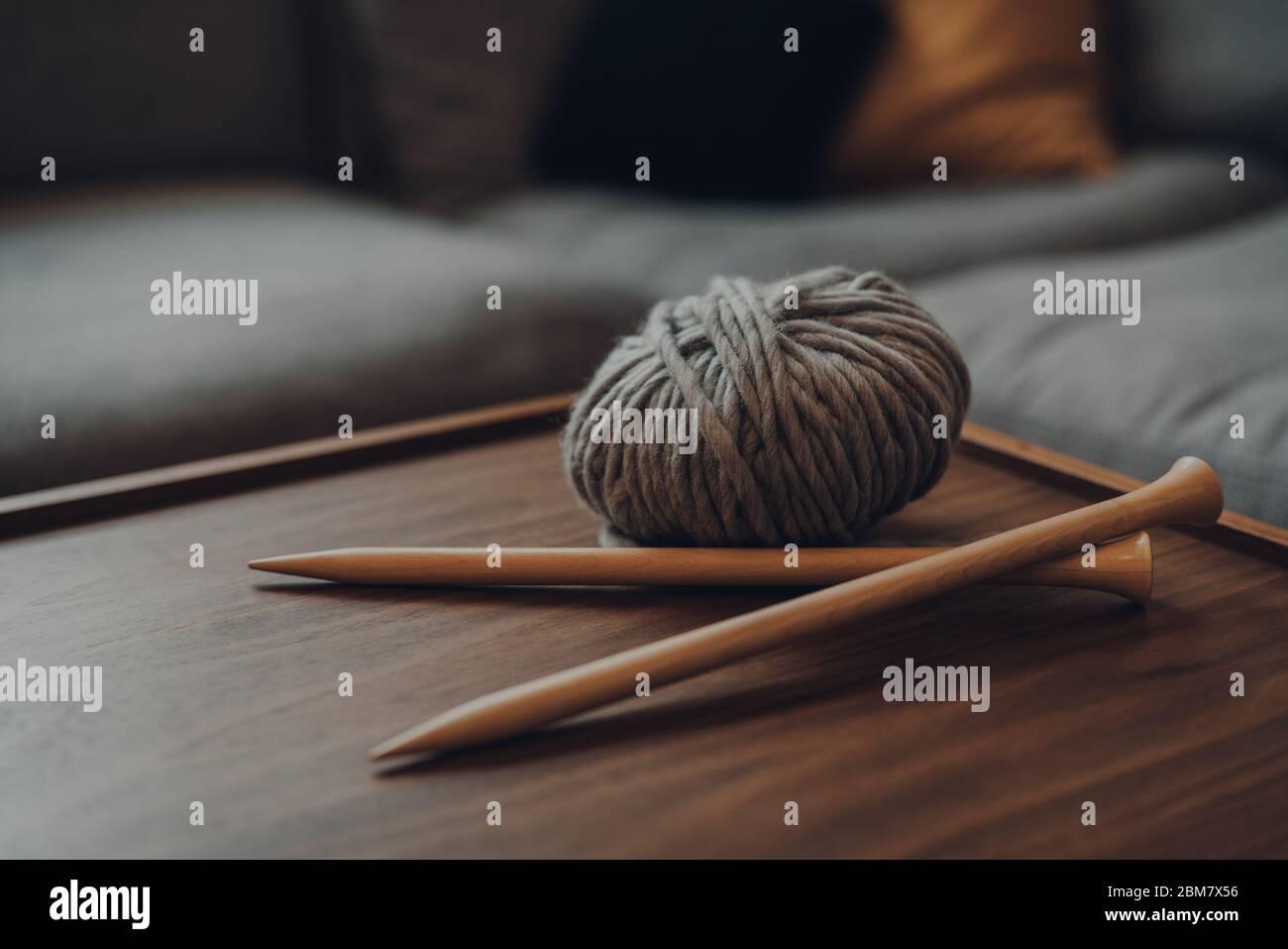 Nahaufnahme einer Kugel aus grauem, grobem Wollgarn und einem Paar gekreuzte große Holzstricknadeln auf einem Holztisch, flacher Fokus, in moderner Scandi-Int Stockfoto