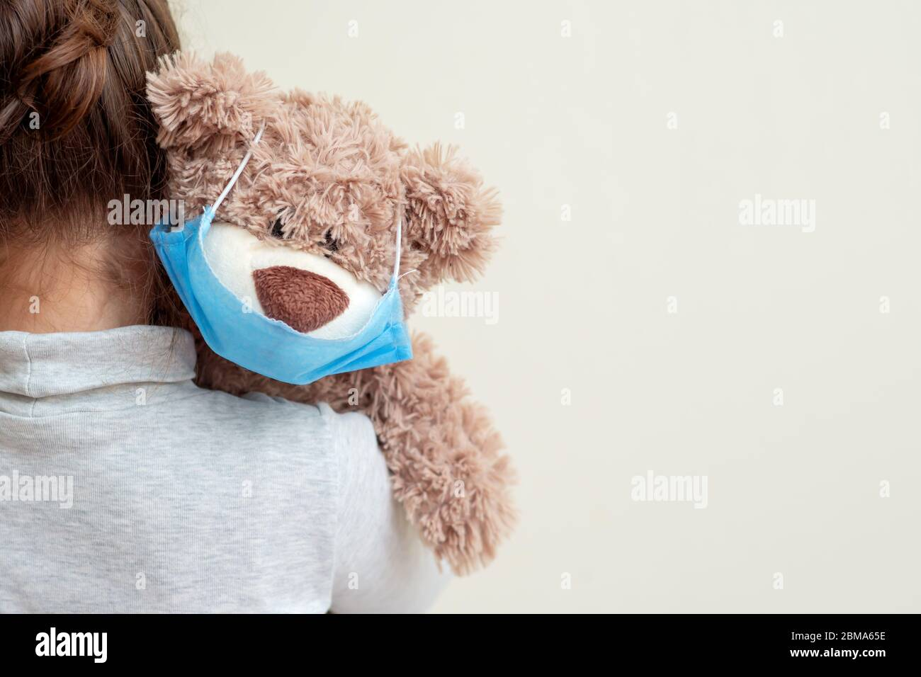 Plüschbär mit schützender medizinischer Maske auf der Schulter des Kindes. Gesundheitsfürsorge und Virenschutz. Stockfoto