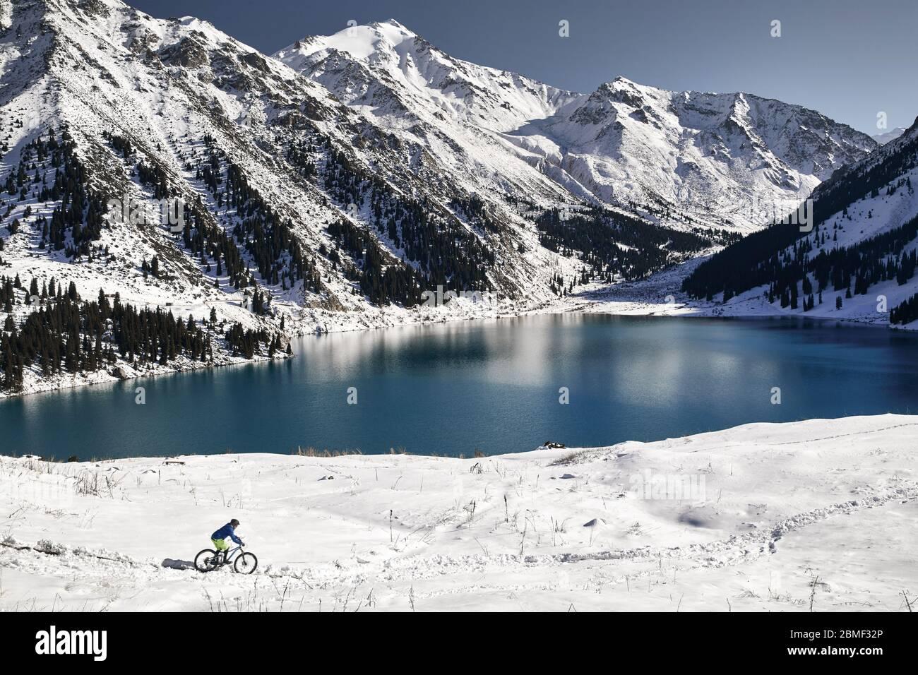 Radfahrer Fahrten auf Schnee Ufer des Bergsees in Almaty, Kasachstan Stockfoto