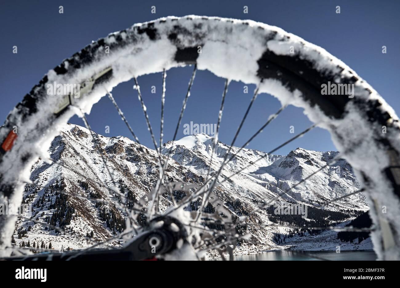 Winter Berglandschaft mit verschneiten Gipfel durch das Fahrrad Rad am grossen See Almaty, Kasachstan Stockfoto