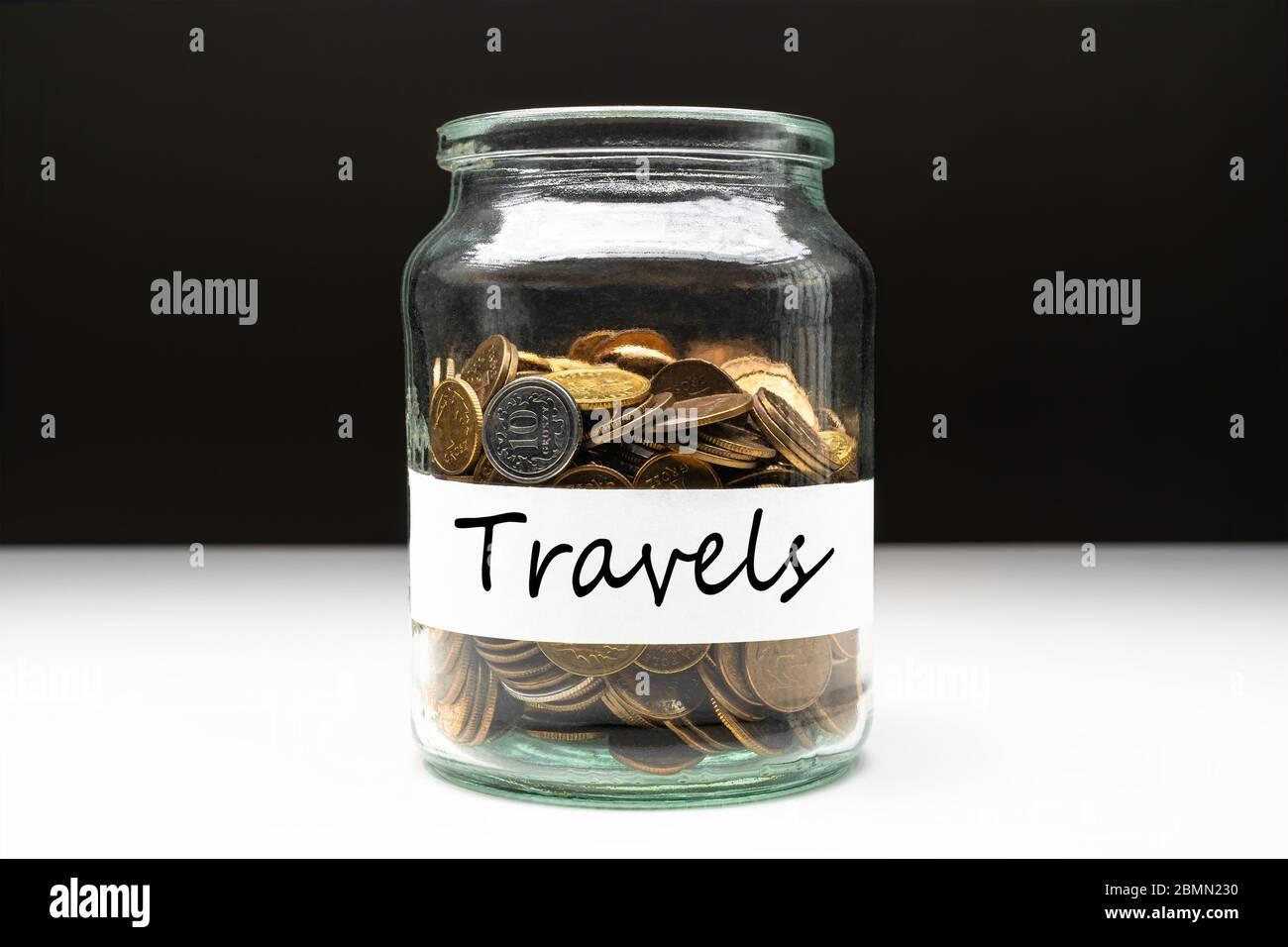 Münzen in einem Glas mit Reisetext auf einem weißen Etikett. Abstraktes Konzept für Einsparungen. Kopierbereich. Stockfoto