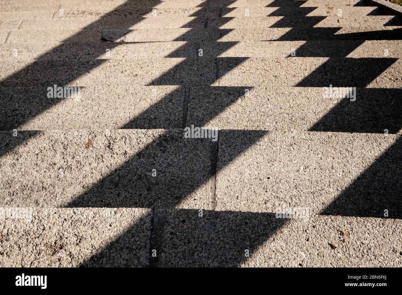 Abstrakter Hintergrund mit einem Muster, das von harten Schatten auf einer Betontreppe in der Stadt geschaffen wurde. Gesehen in Deutschland im Mai. Stockfoto