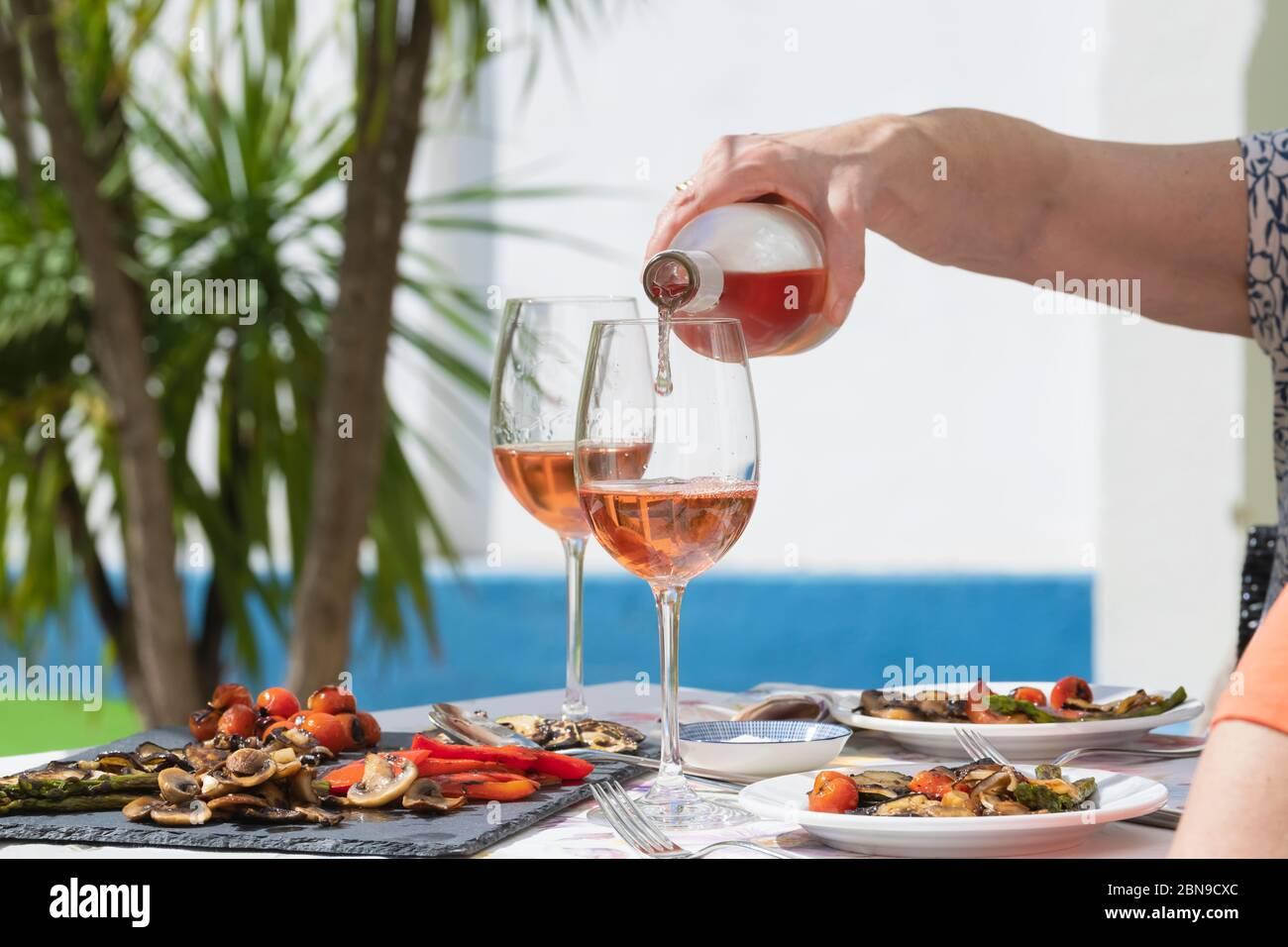 Eine Hand der Frau, die Roséwein ausgießt Stockfoto