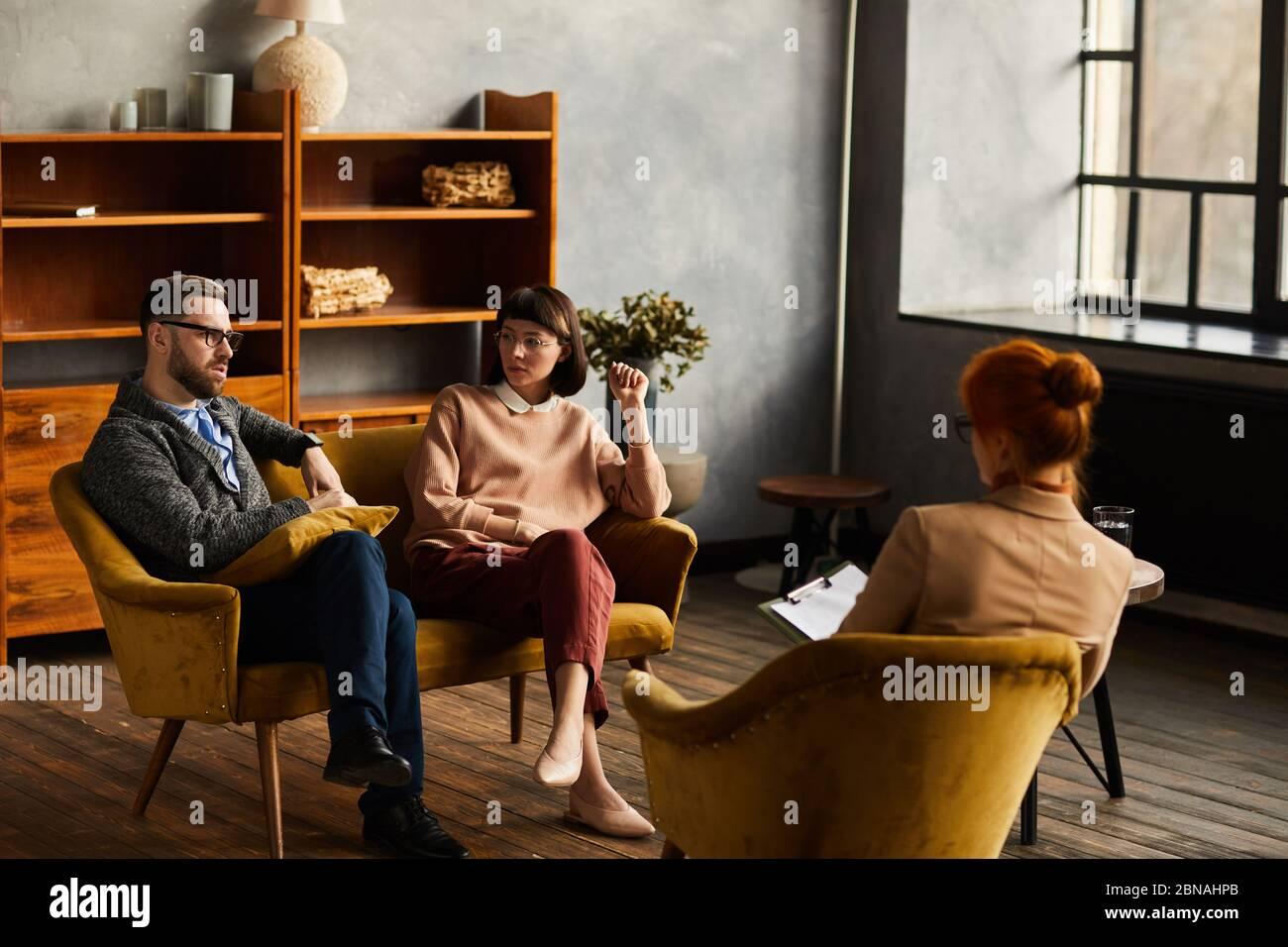 Gruppe von Geschäftsleuten, die auf Sesseln sitzen und zukünftige Pläne während einer Besprechung im Büro besprechen Stockfoto