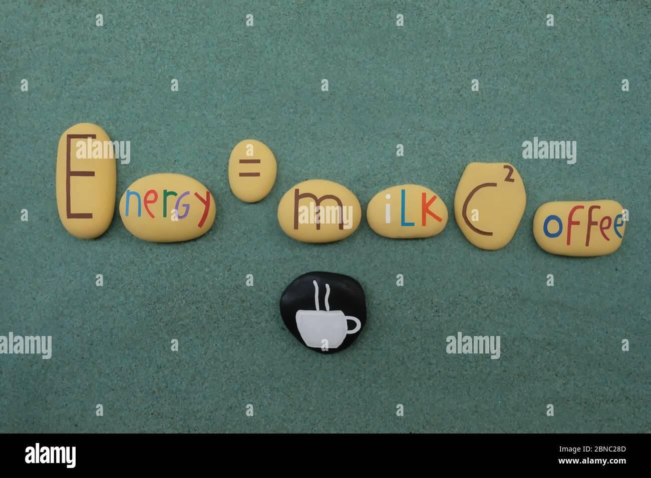 Einsteins Gleichung, angepasst an die Kaffeeleistung mit kreativen Steinen über grünem Sand Stockfoto
