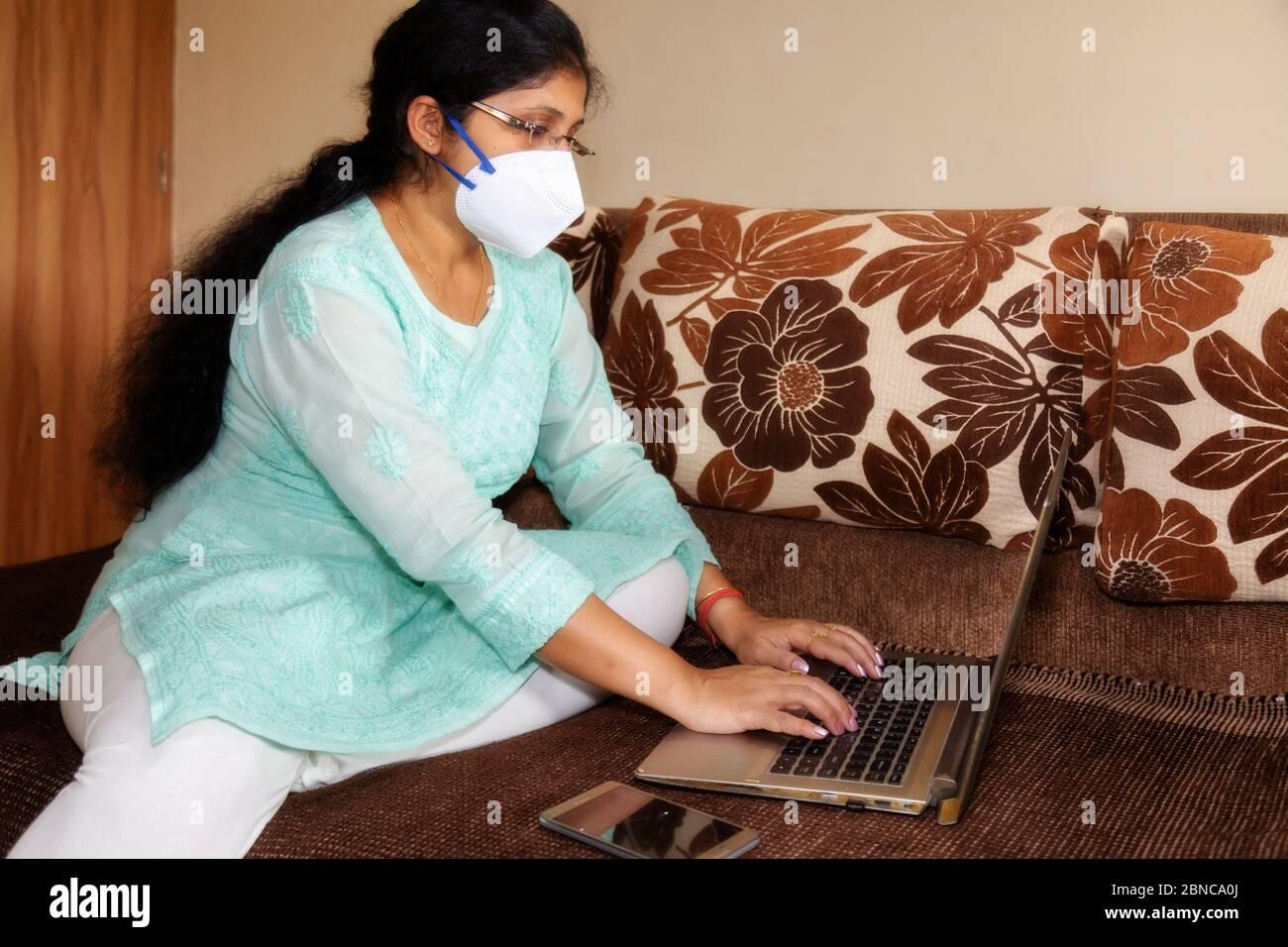 Indische Frau in schützenden Gesichtsmaske Arbeit von zu Hause aus während Coronavirus Sperre nach unten Stockfoto