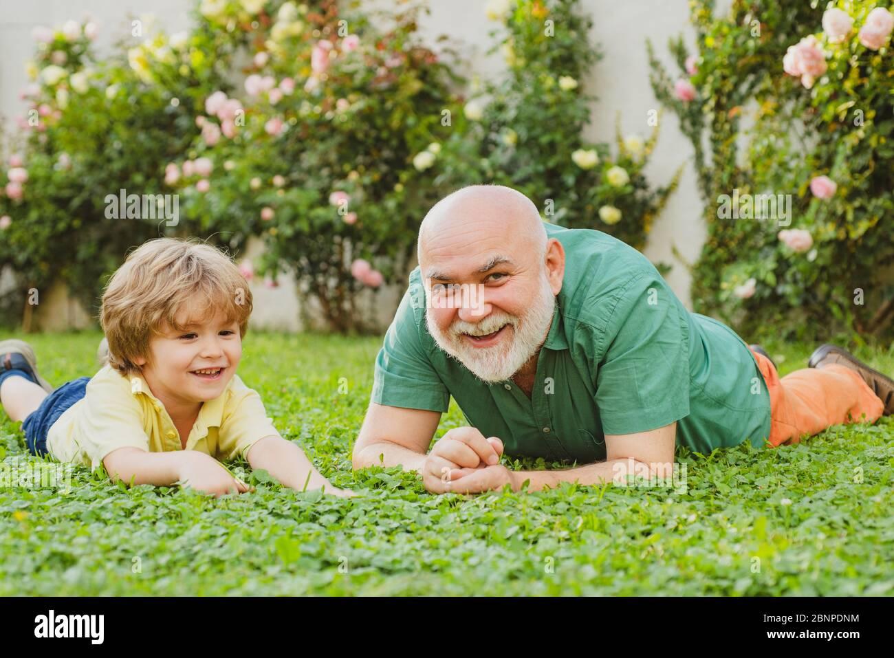 Enkel umarmen seinen Großvater. Glückliche Familie Vater und Kind auf Wiese mit einem Drachen im Sommer auf grünem Gras. Niedlicher Junge mit Papa spielen im Freien Stockfoto