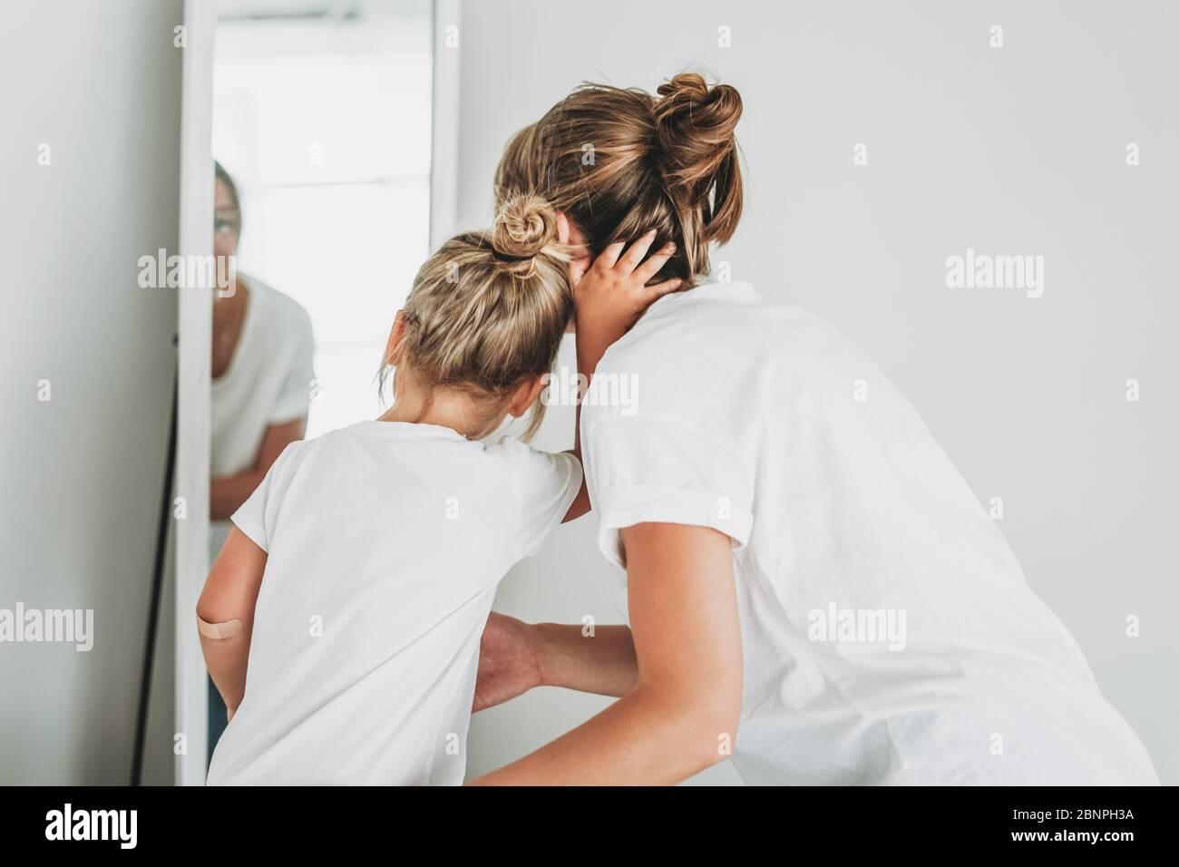 Junge Mutter und Tochter in weißen T-Shirts schauen in den Spiegel, Menschen von hinten Stockfoto