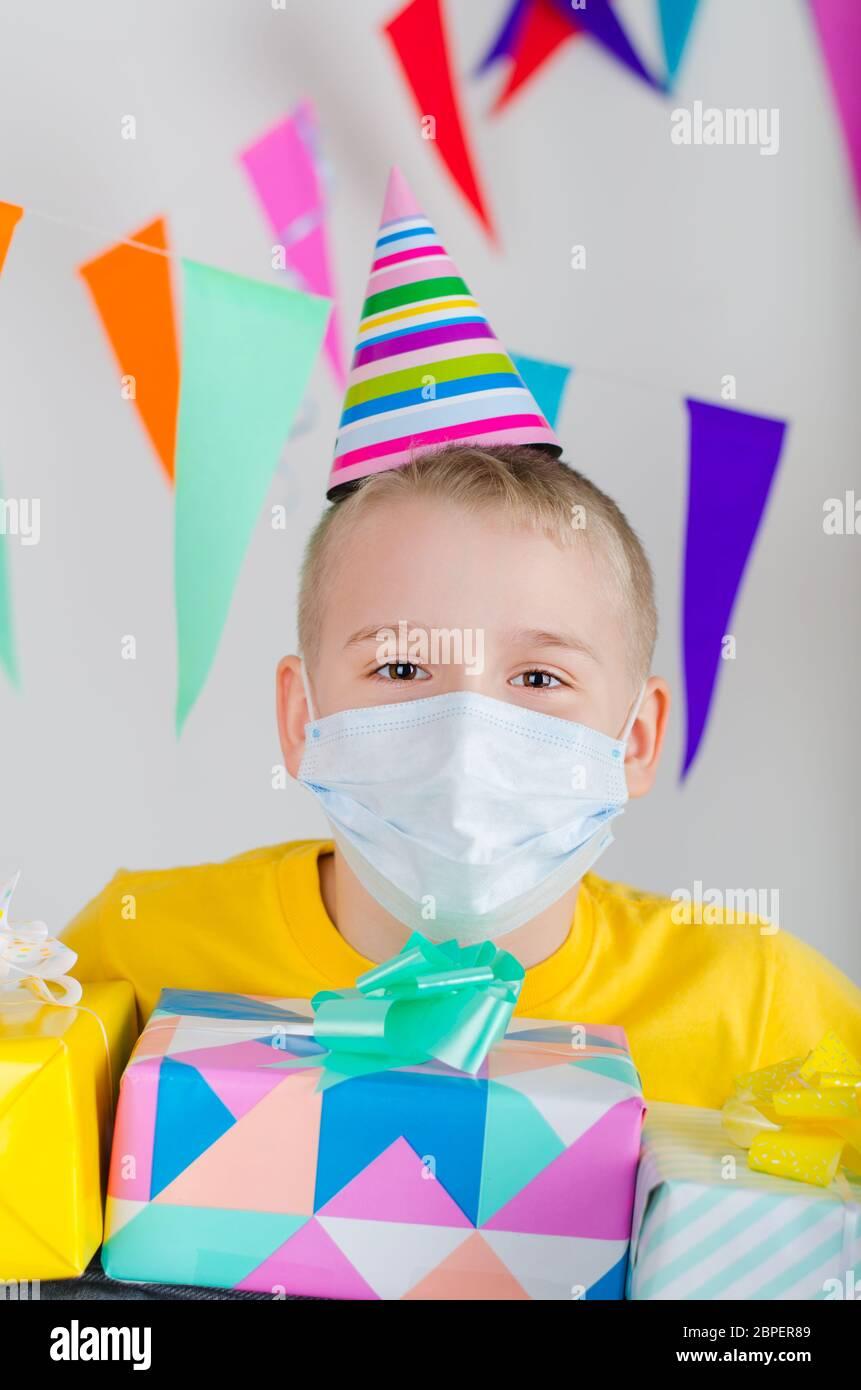 Happy Boy in Medizin Gesichtsmaske und festliche Mütze mit Geschenken in der Hand feiert Geburtstag. Geburtstag allein in Isolation sperren. Soziale Distanz. Stockfoto