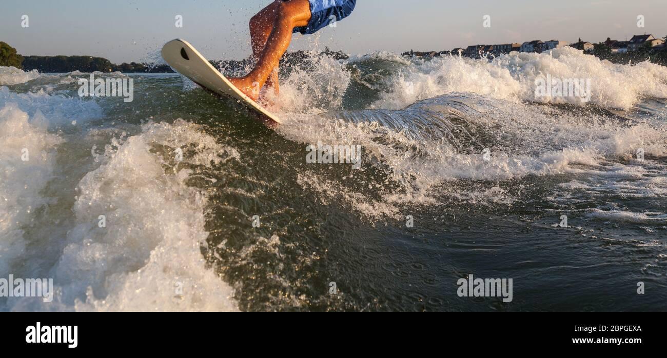 Mann Surfen auf dem Wakeboard von einem Motorboot über das Boot gezogen Welle Wakeboarder Surfen Spaß Freizeit Aktivität Familienausflug Wassersport er sportlich Stockfoto