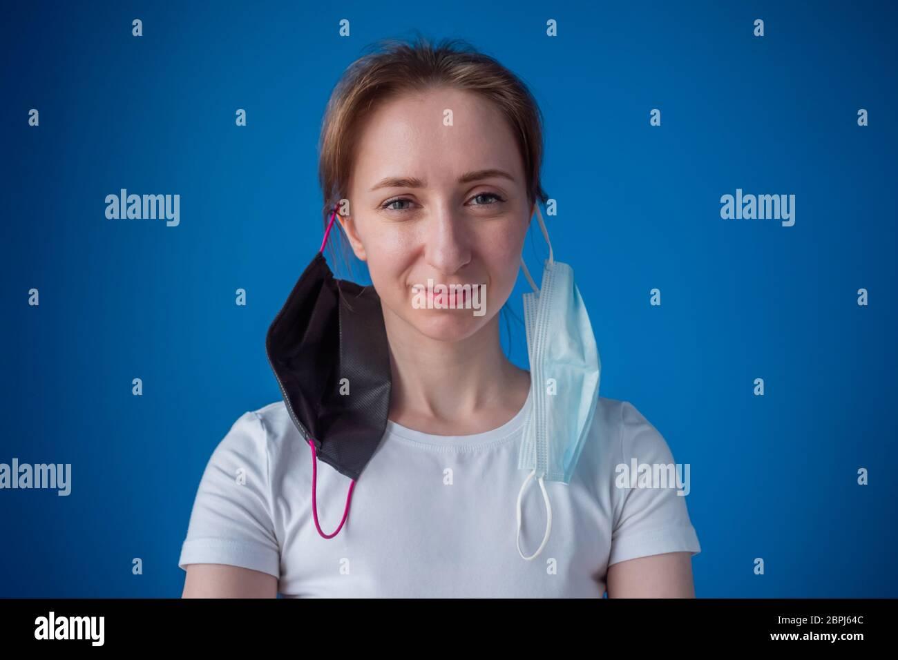 Porträt von lustigen Frau mit zwei medizinischen Gesichtsmaske an den Ohren hängen, Blick auf Kamera im Zimmer mit blauer Wand zu Hause. Selbstisolierung, Prävention Stockfoto