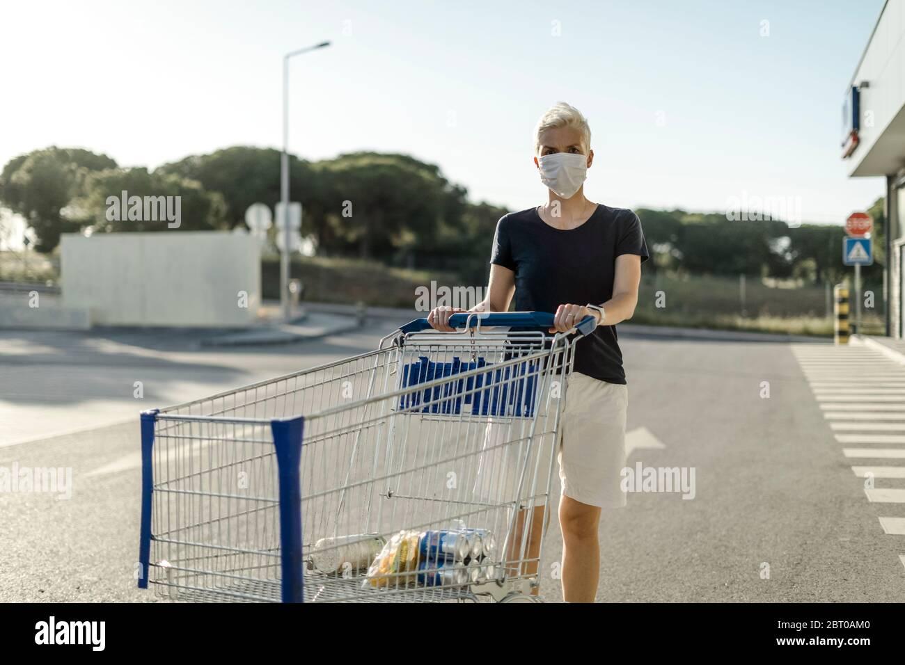 Frau mit schützender Gesichtsmaske mit Warenkorb vor dem Supermarkt Stockfoto