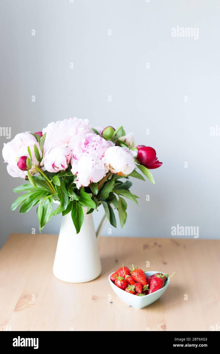 Bündel rosa Pfingstrosen in Vase und Erdbeere auf dem Holztisch. Blumen auf einem beigefarbenen Holztisch neben dem Fenster. Haus innen. Wunderschön Stockfoto