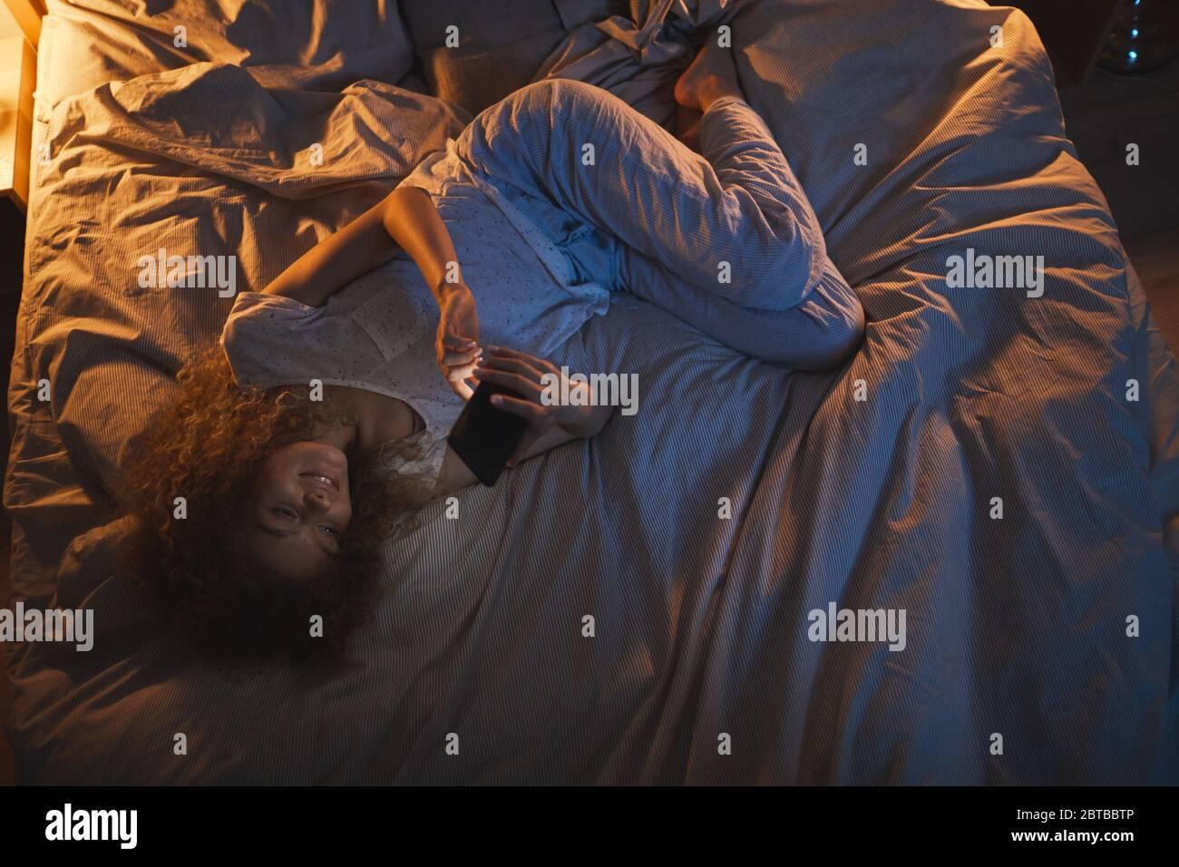 Draufsicht auf junge Frau, die nachts auf dem Bett liegt und Smartphone benutzt, während sie dem Freund SMS schreibt, Raum kopieren Stockfoto