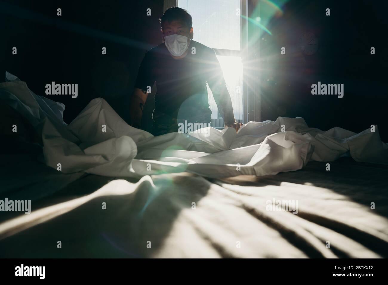 Asiatischer Mann putzt Bett am Morgen. Das Haus hält aktiv. Schlafzimmer hat das Sonnenlicht. Stockfoto
