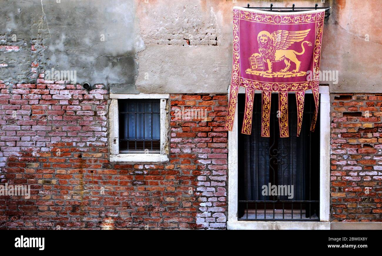 Die venezianische Flagge mit dem symbolischen 'geflügelten Löwen', bekannt als das Banner des Hl. Markus, ist stolz ausgestellt. Stockfoto