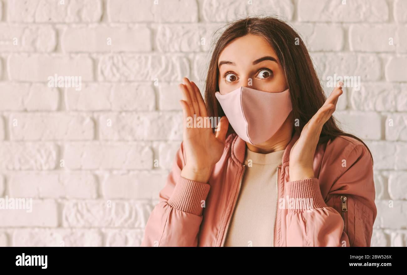 Portrait junge schöne Hipster Mädchen in stilvollen medizinischen Gesichtsmaske fühlen sich aufgeregt oder schockiert. Glücklich erstaunt Frau in rosa Schutzmaske fühlen s Stockfoto