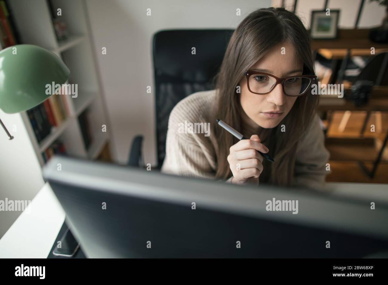 Junge Frau, die von ihrem Home Office aus am Computer arbeitet Stockfoto