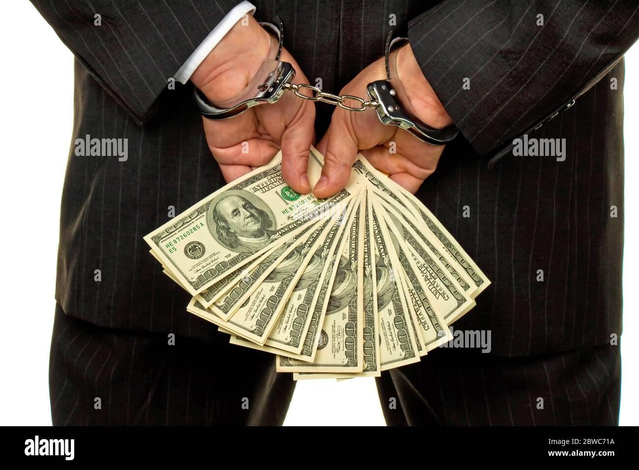 Manager mit Dollar Geldscheinen in der Hand, Handschellen, verhaftet, Schwarzgeld, Stockfoto