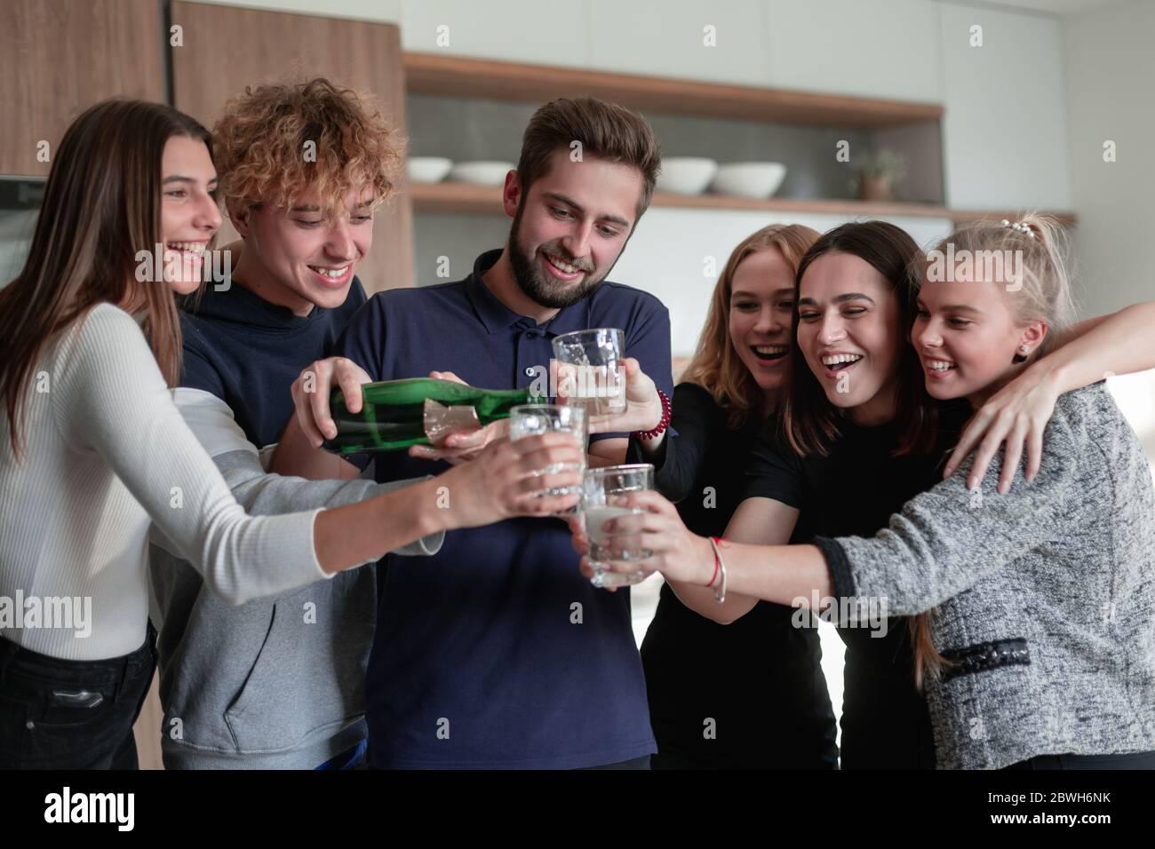 Fröhliche junge Freunde, die eine Flasche Champagner öffnen Stockfoto