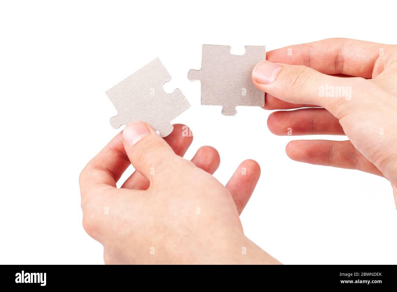 Hände zusammen, Verbindung zwei passende leere Puzzle-Teile, Fügen entsprechende Teile, Elemente isoliert auf weiß, ausgeschnitten Stockfoto
