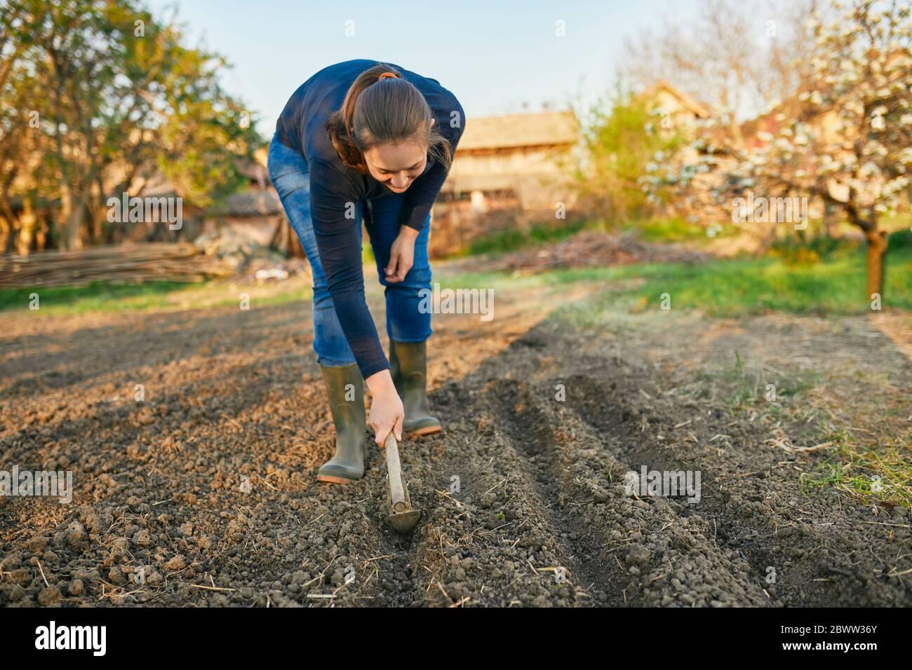 Volle Länge der Frau mit Hand Pflug auf dem Boden während der Gartenarbeit am Wochenende Stockfoto