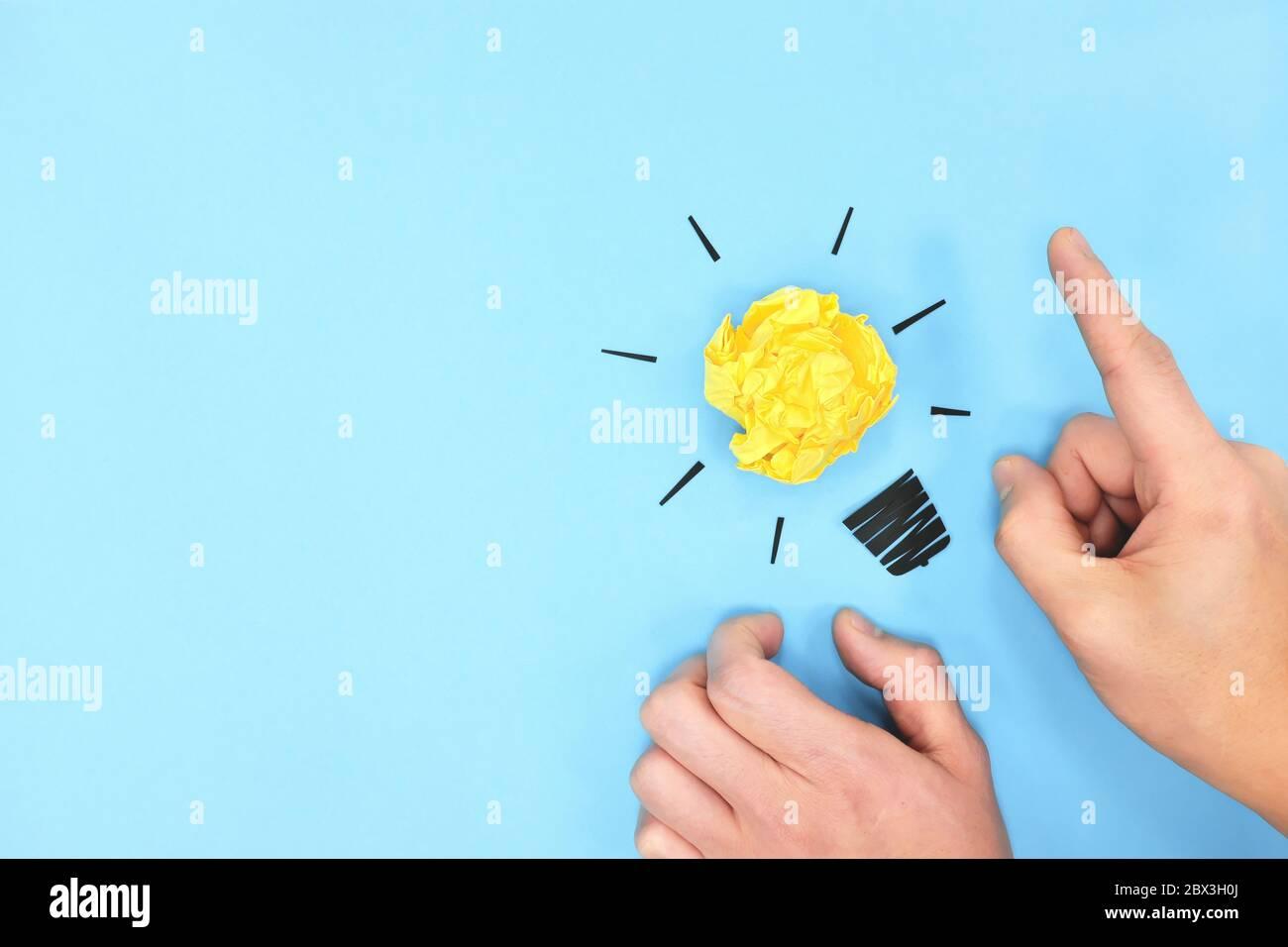 Gelbe Glühbirne in blauem Hintergrund flach gelegt. Strahlende neue Ideen und denkende Lösungskonzepte. Stockfoto