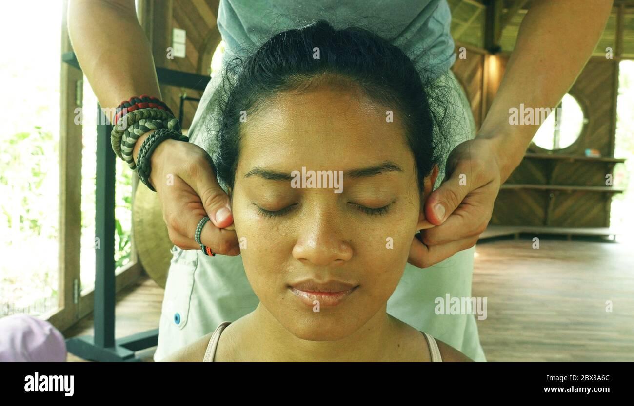 Nahaufnahme Gesicht Porträt der jungen wunderschönen und entspannten asiatischen indonesischen Frau erhalten traditionelle Gesichts Thai-Massage mit männlichen Händen arbeiten ihre Ohren Stockfoto