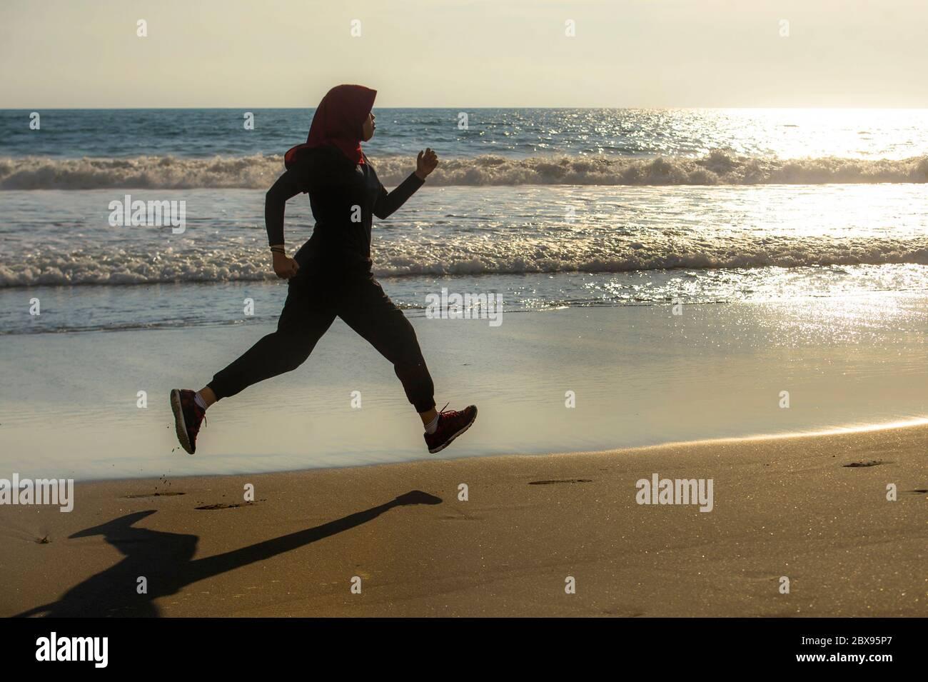 Junge gesunde und aktive Läufer muslimische Frau im Islam hijab Kopftuch Laufen und Joggen am Strand tragen traditionelle arabische Sportkleidung in fitn Stockfoto