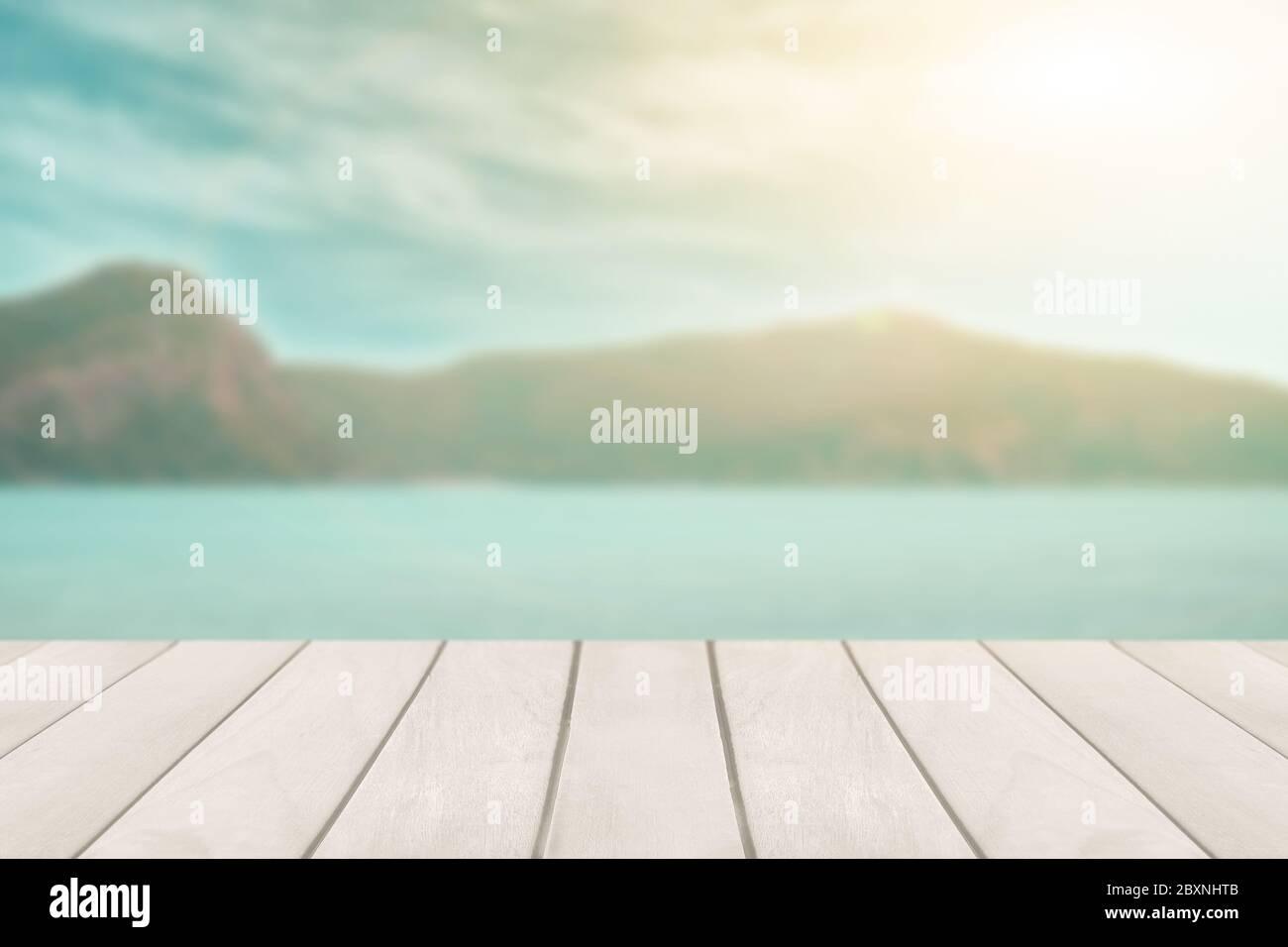 Perspektive leere weiße Holztisch auf der Oberseite über verschwommene Seascape Hintergrund. Für die Montage von Produkten Display oder Design-Layout. Stockfoto