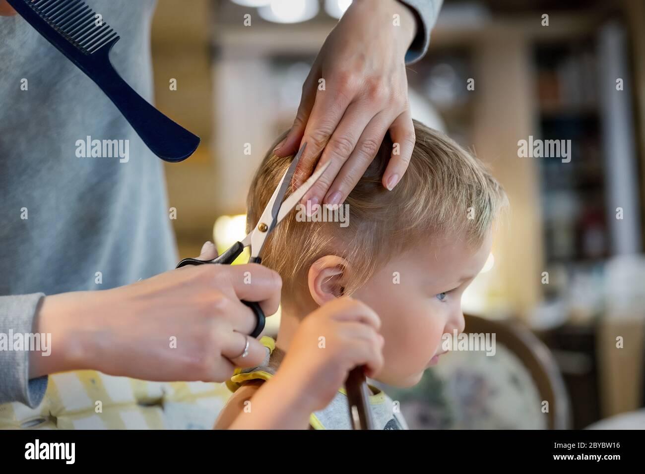Close-up junge Erwachsene kaukasische Mutter machen Haarschnitt fot niedlich liebenswert Sohn Kleinkind Junge zu Hause durch Quarantäne und Sperrung. Mutter schneiden Haare des Kindes Stockfoto