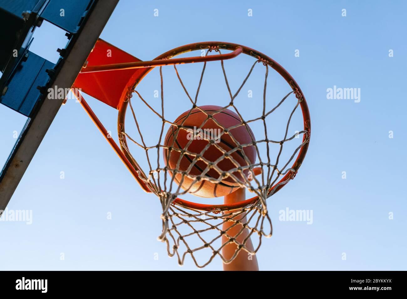 Street Basketball Slam Dunk Wettbewerb. Nahaufnahme des Balls, der in den Reifen fällt. Urban Jugend Spiel. Konzept des Erfolgs, Punkte sammeln und gewinnen Stockfoto