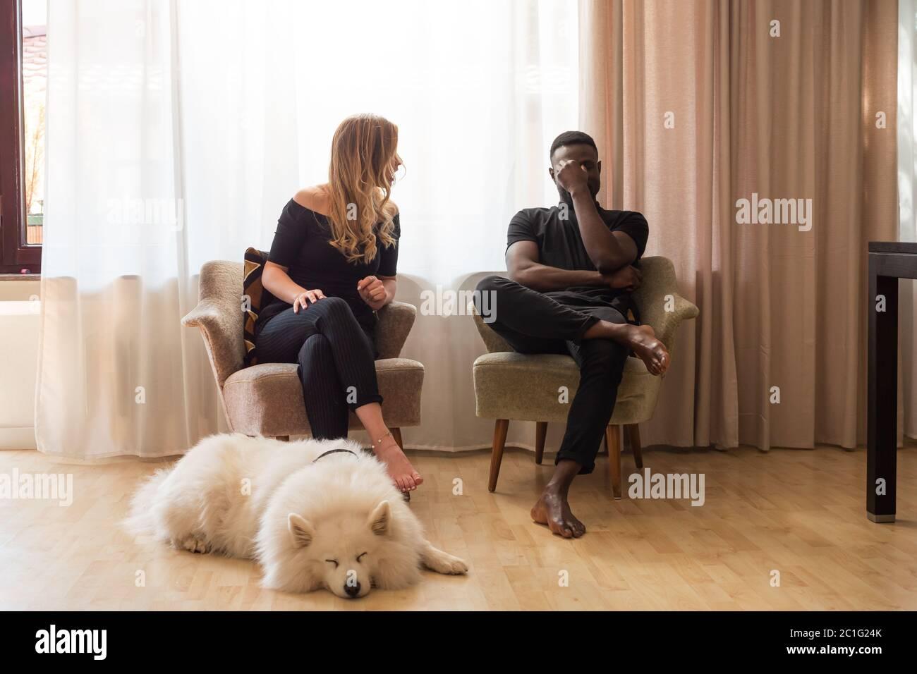 Mann und Frau streiten sich auf Wohnzimmersesseln mit Hund schlafen vor. Stockfoto