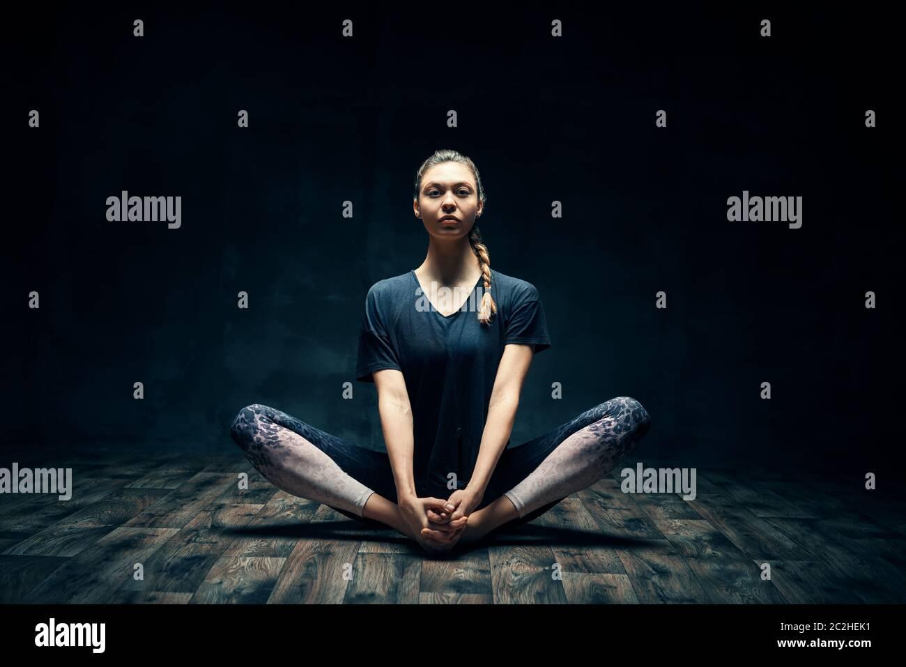 Junge Frau, die Yoga praktiziert, posiert auf dunklem Raum Stockfoto