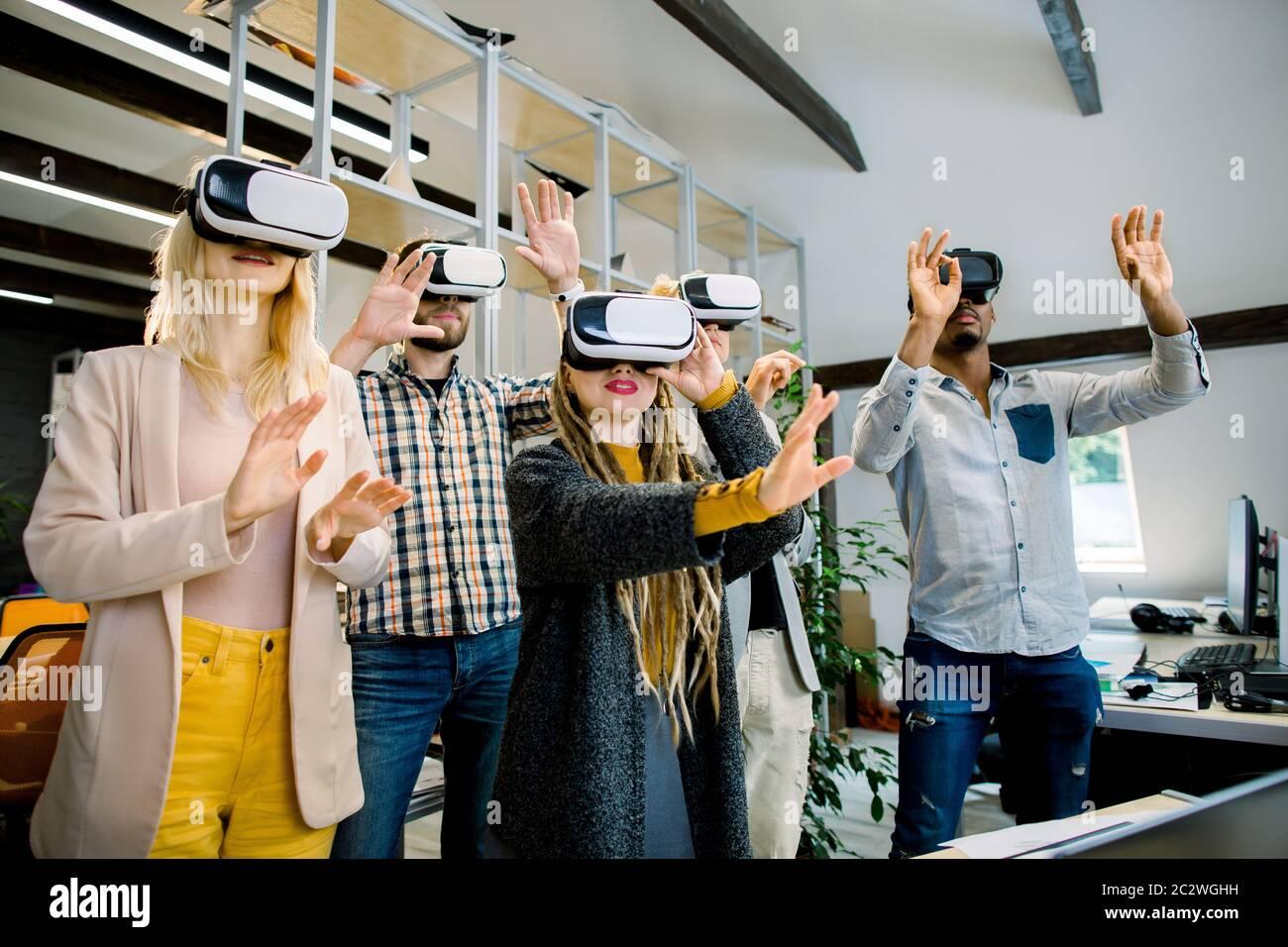 Team von fünf jungen multiethnischen Entwicklern in Freizeitkleidung arbeiten mit Virtual-Reality-Brille während eines Geschäftstreffens. Junge Kollegen aus der Wirtschaft Stockfoto