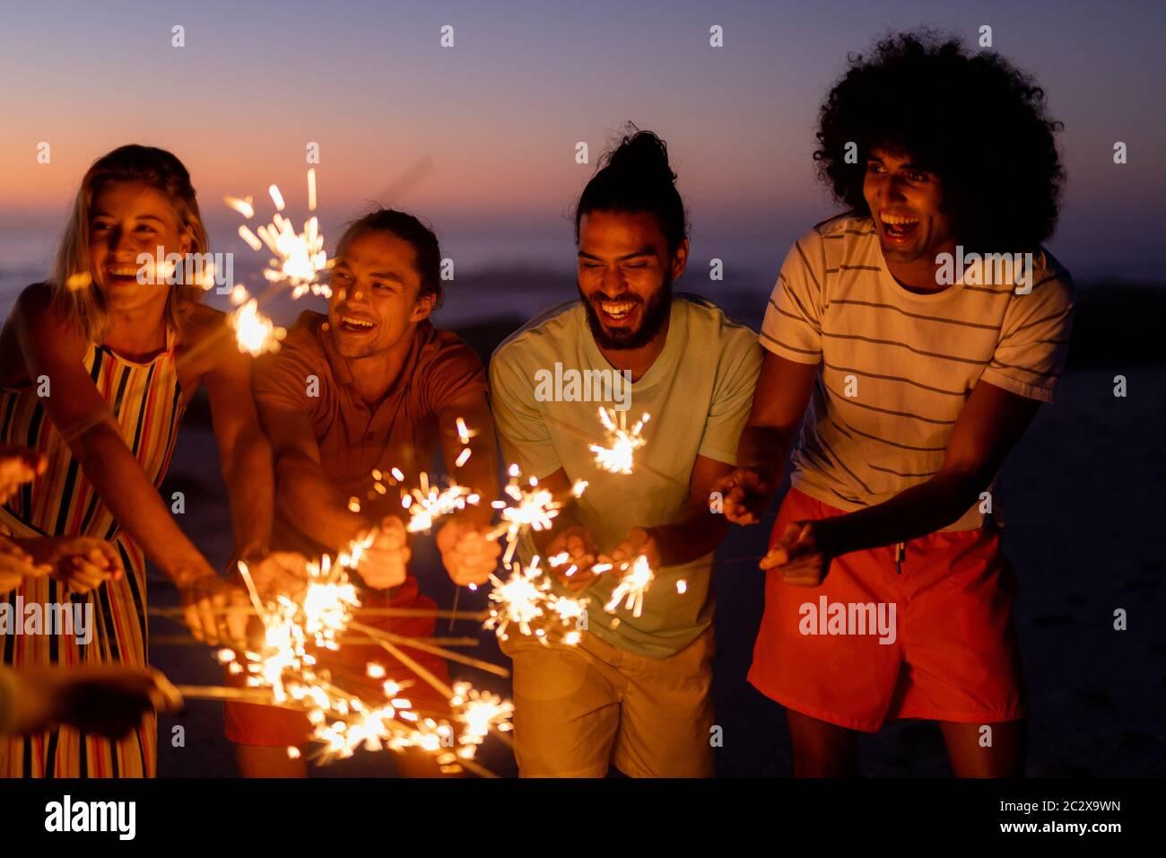 Multiethnische Gruppe von männlichen und weiblichen Tänzen mit Feuerwerkskörper Stockfoto
