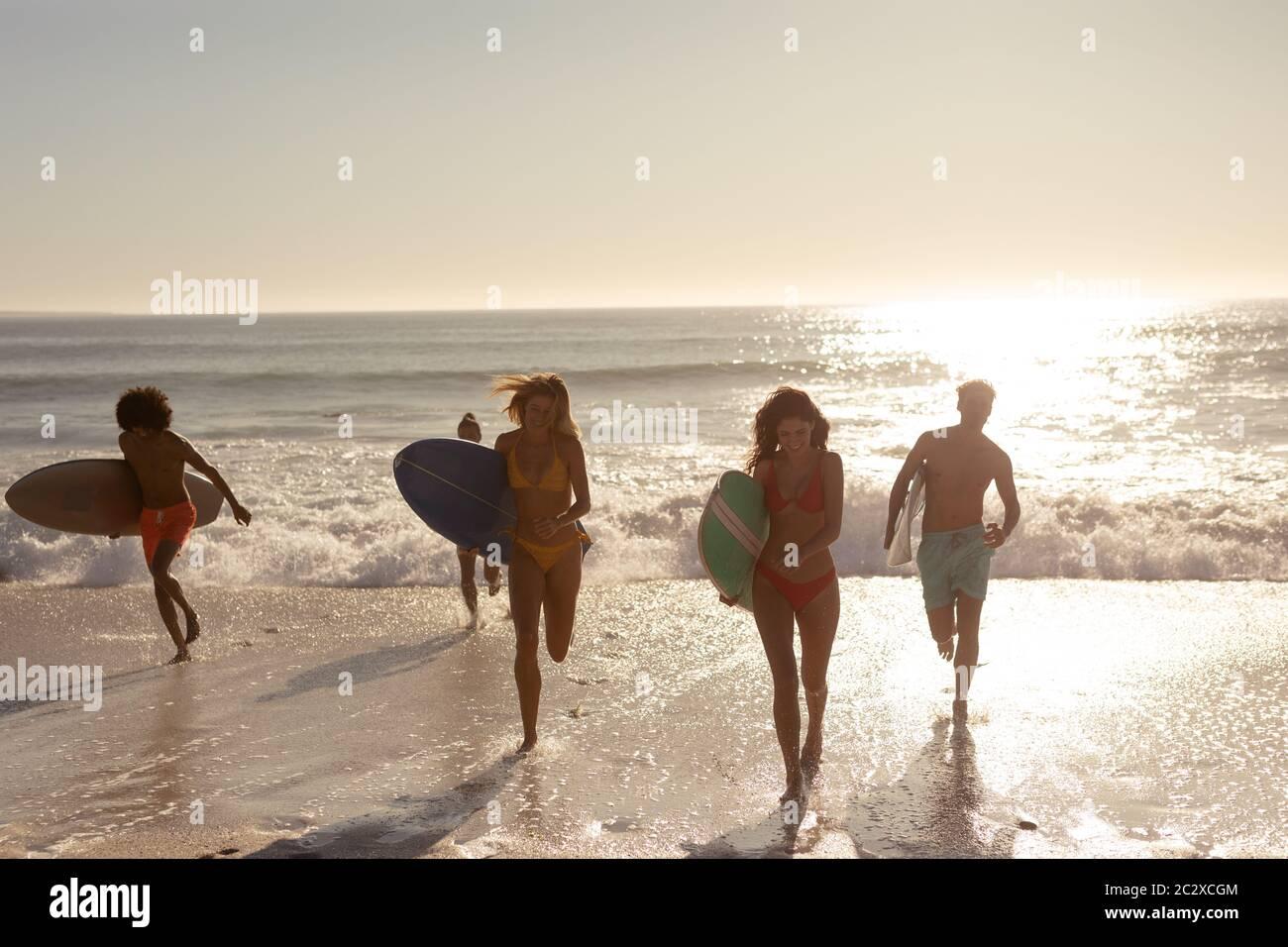 Multiethnische Gruppe von Männern und Frauen, Surfen am Strand Stockfoto