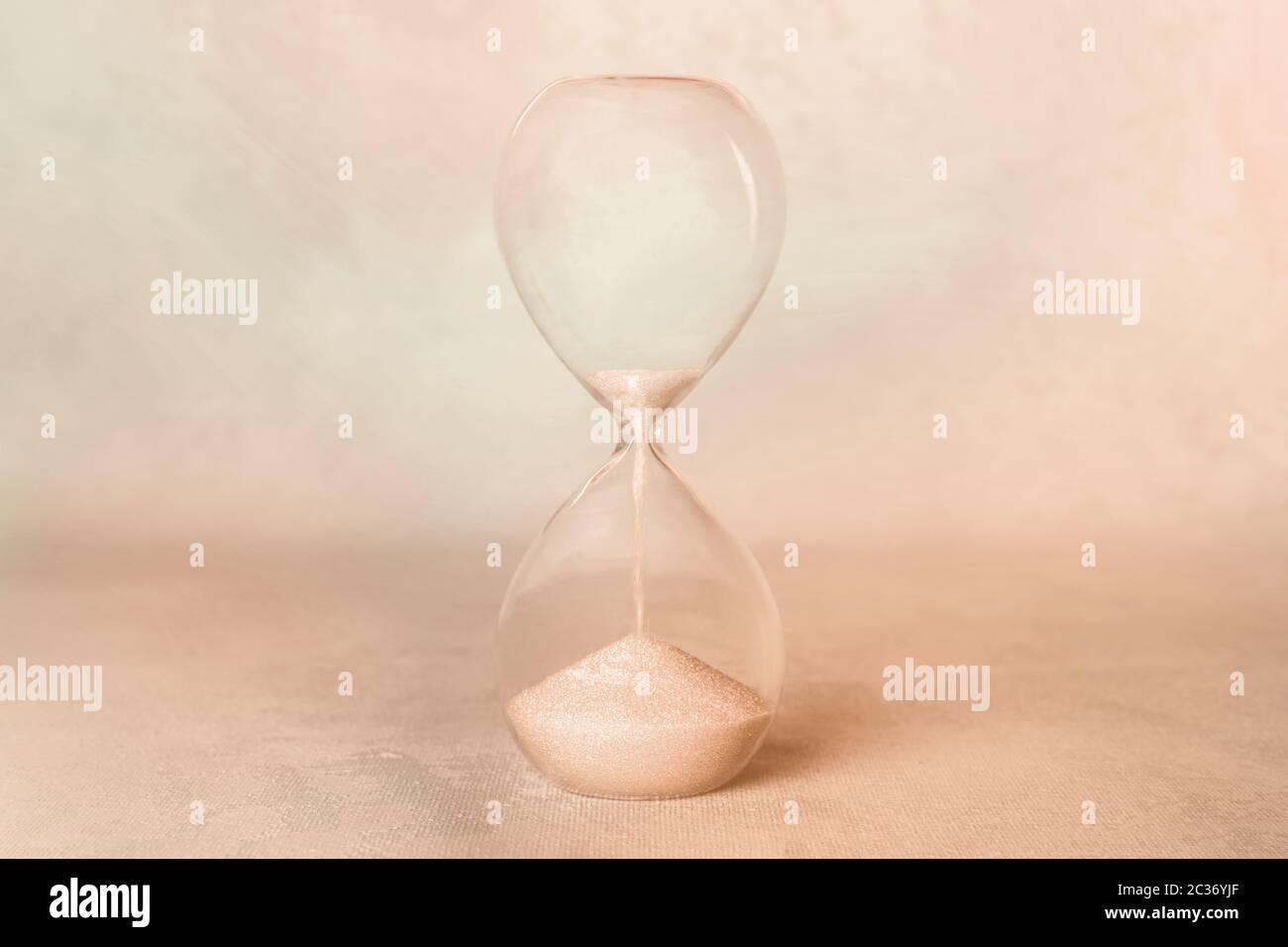 Zeit. Eine Sanduhr mit durchfallendem Sand. Alter, Nostalgiekonzept, sepiagetöntes Bild Stockfoto