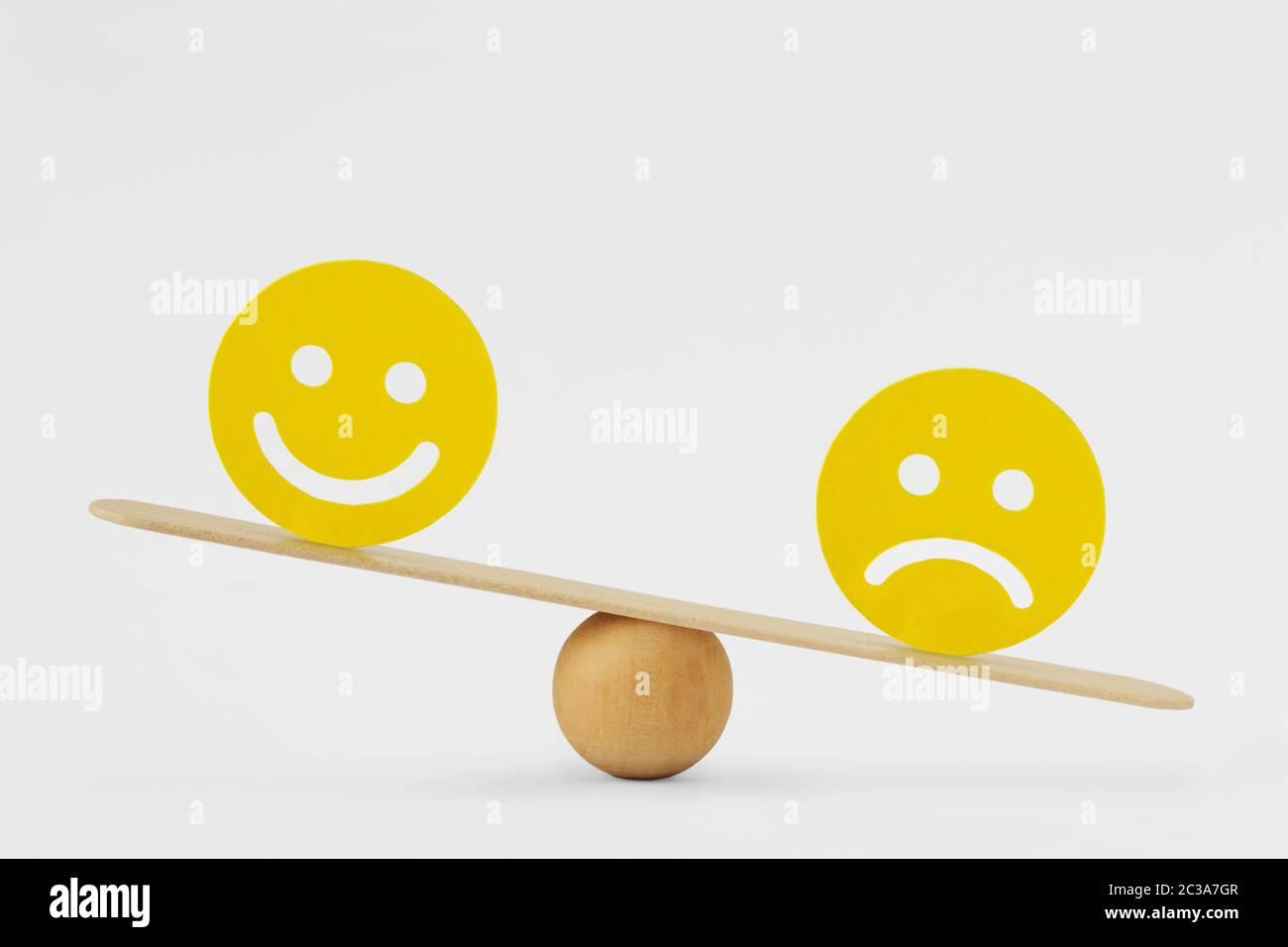 Smiley Face und trauriges Face auf der Skala - Konzept der Traurigkeit als vorherrschende Emotion Stockfoto
