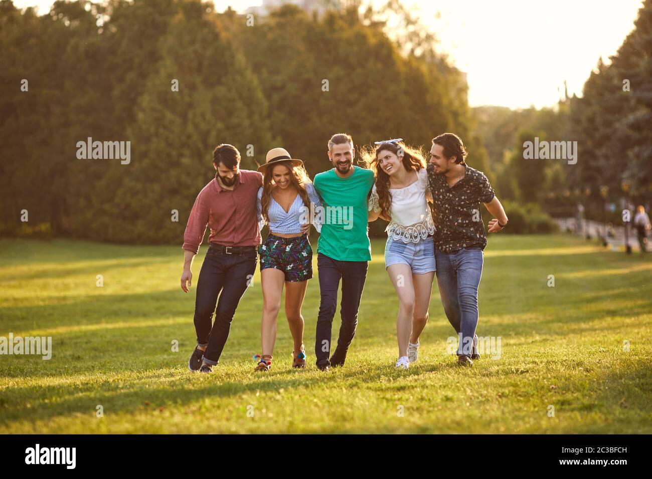 Eine Gruppe von Freunden umarmt sich während ihres Spaziergangs in der Landschaft am Sommertag. Fröhliche Leute, die ihr Wochenende draußen genießen Stockfoto