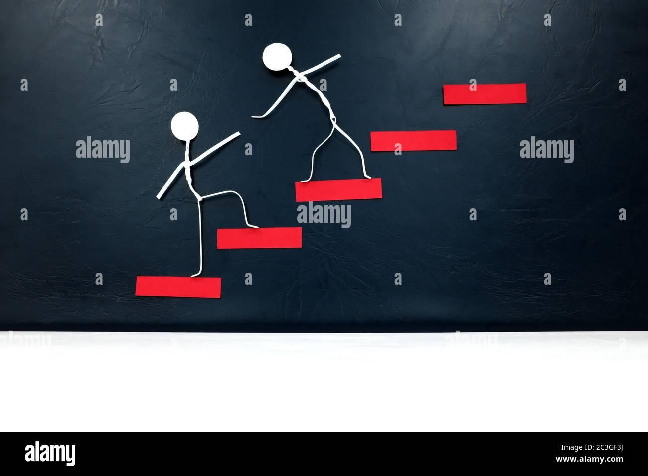 Helfende Hand, Unterstützung und Teamwork Konzept. Zwei menschliche Stockfiguren, die eine rote Leiter klettern. Stockfoto