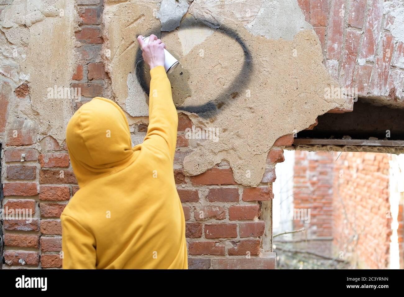 Ein Teenager zeichnet an einer Wand eines verlassenen Gebäudes Eine Sprühdose Farbe Stockfoto