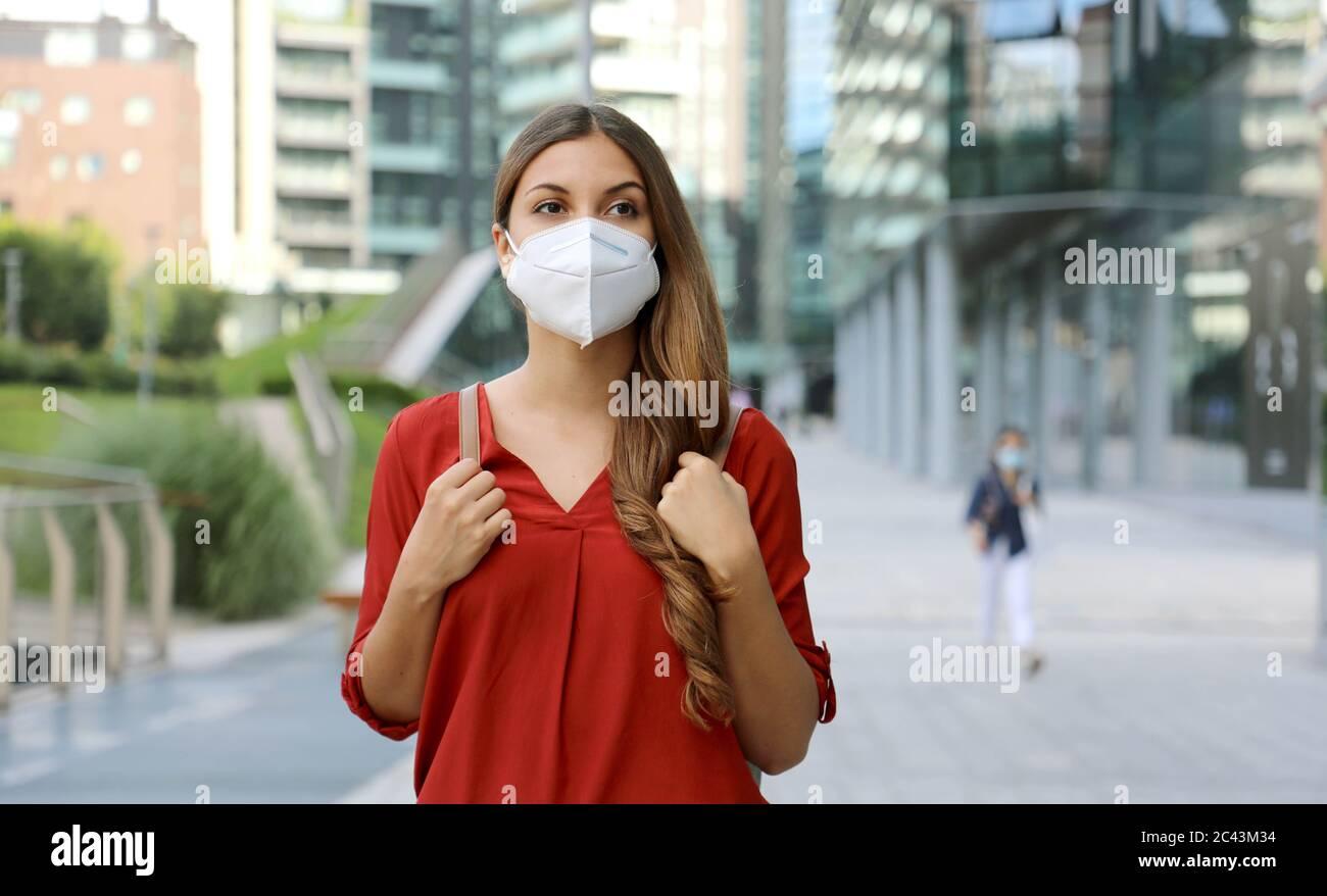 Junge Frau trägt Schutzmaske KN95 FFP2 zu Fuß in der modernen Stadt Straße. Studentin mit Gesichtsmaske gegen Coronavirus-Krankheit 2019 (COVID-19). Stockfoto