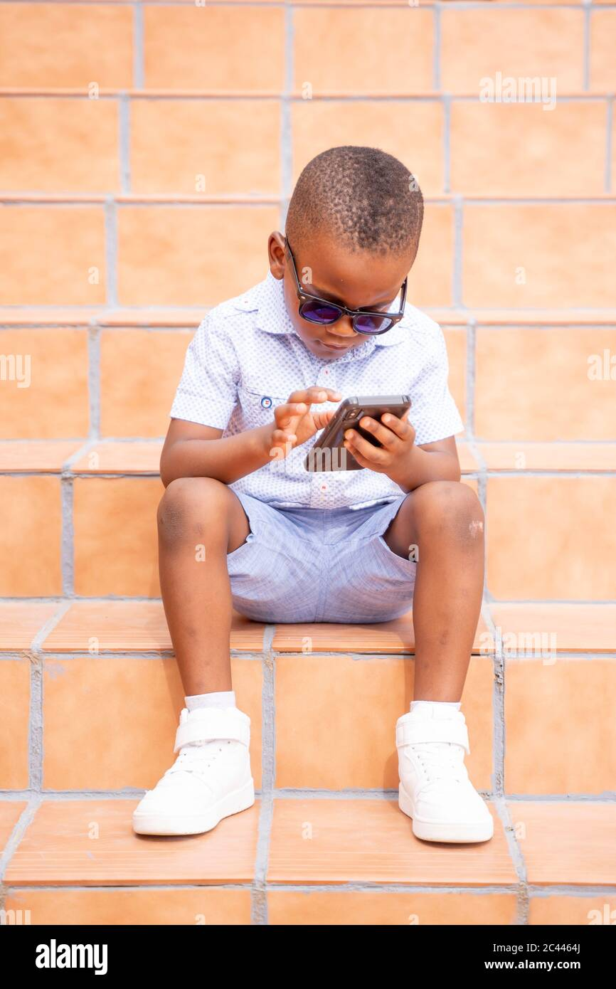 Portrait von kühlen kleinen Jungen trägt Sonnenbrille auf Treppen im Freien mit Handy sitzen Stockfoto