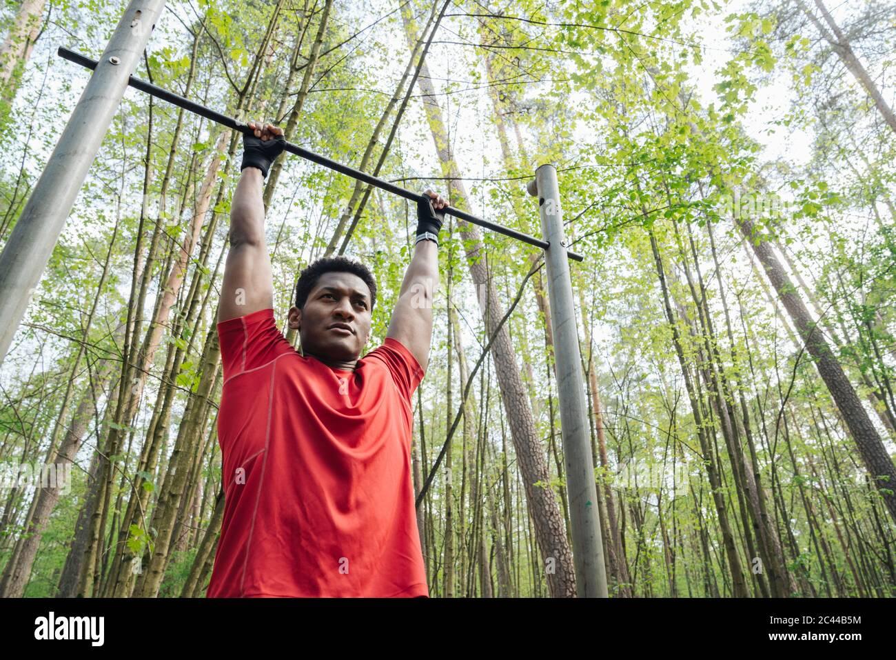 Sportler trainieren an der High Bar im Wald Stockfoto