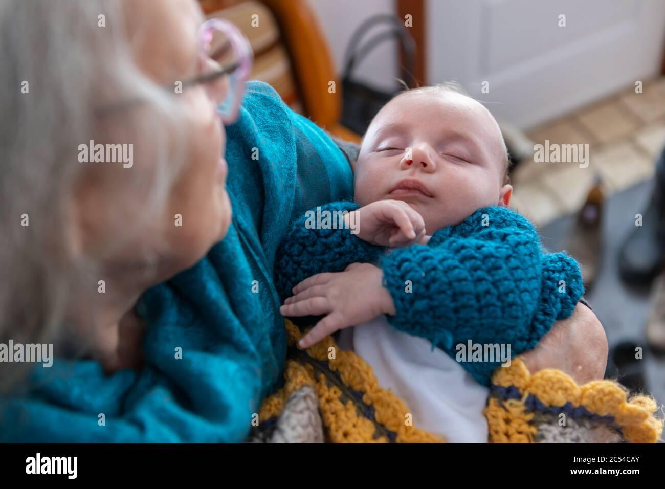 Selektive Fokusaufnahme eines kleinen Jungen, der in den Armen seiner Großmutter schläft. Aus der Fokussierung oben links schaut der stolze Senior auf das Kind Stockfoto