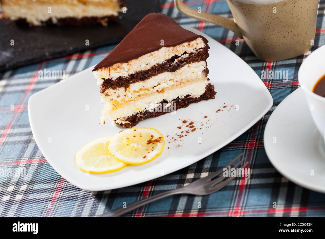 Zitrone - Schokolade Kuchen mit Biskuitteig serviert mit Zitronenscheiben auf Platte Stockfoto
