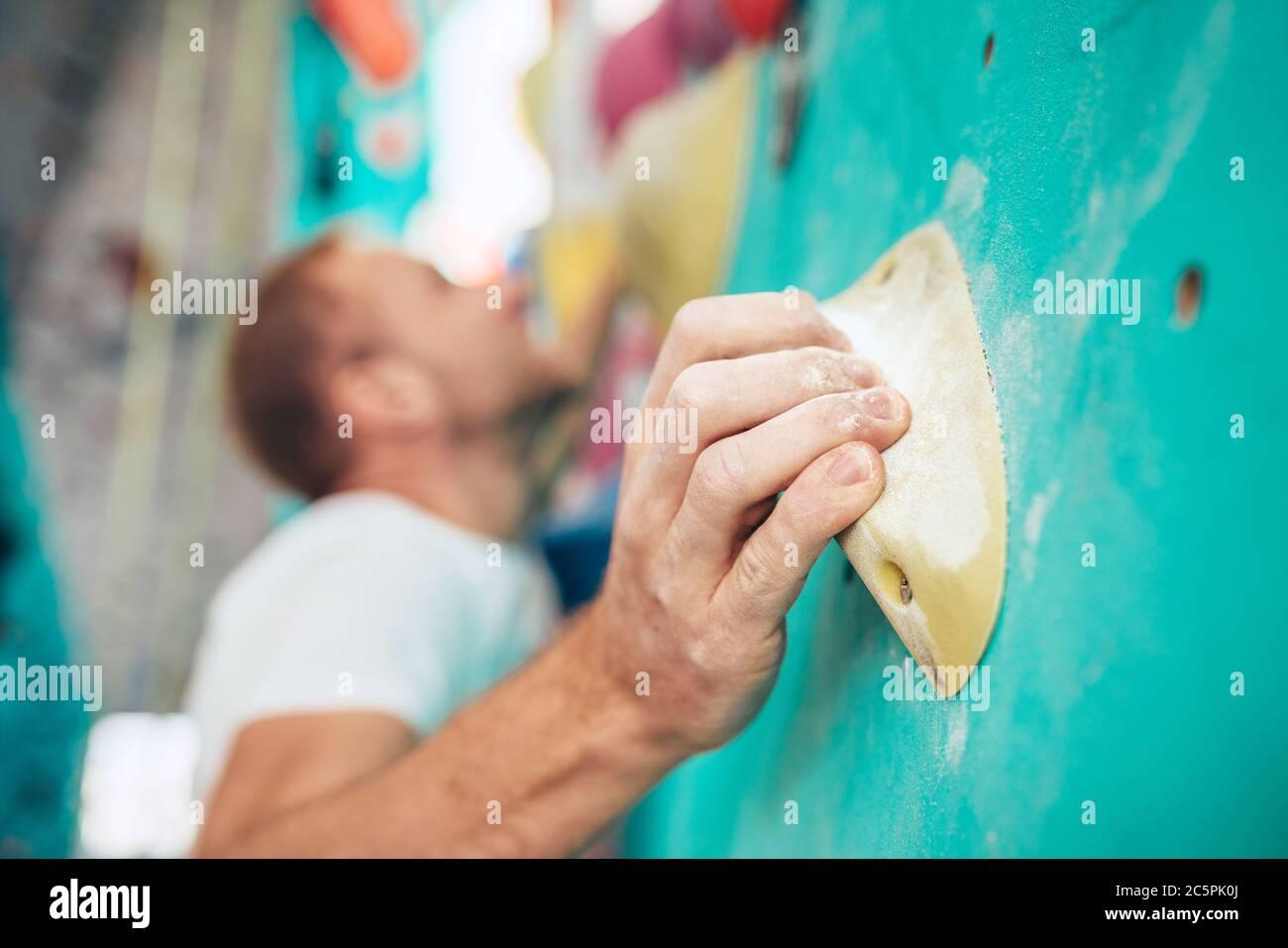 Nahaufnahme von Kreide (Magnesium) bedeckte die Handfläche des Mannes, der das Indoor-Klettergriffelement anklammerte, während der Mann aufkletterte. Unfokussierte Kletterer Gesicht auf dem Rücken Stockfoto