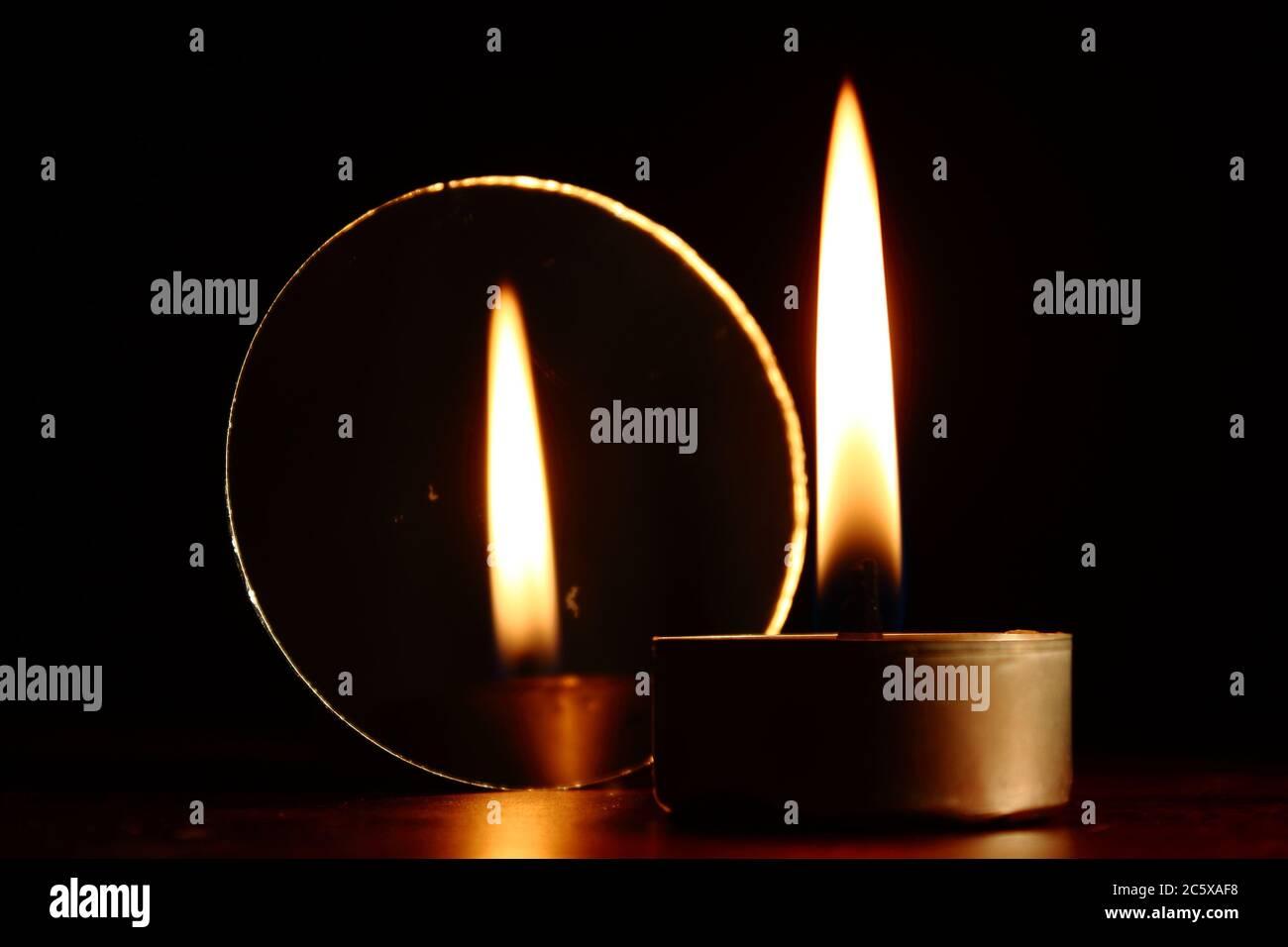 Brennende Kerze neben einem Spiegel, der seine Spiegelung zeigt, dunkler Hintergrund Stockfoto