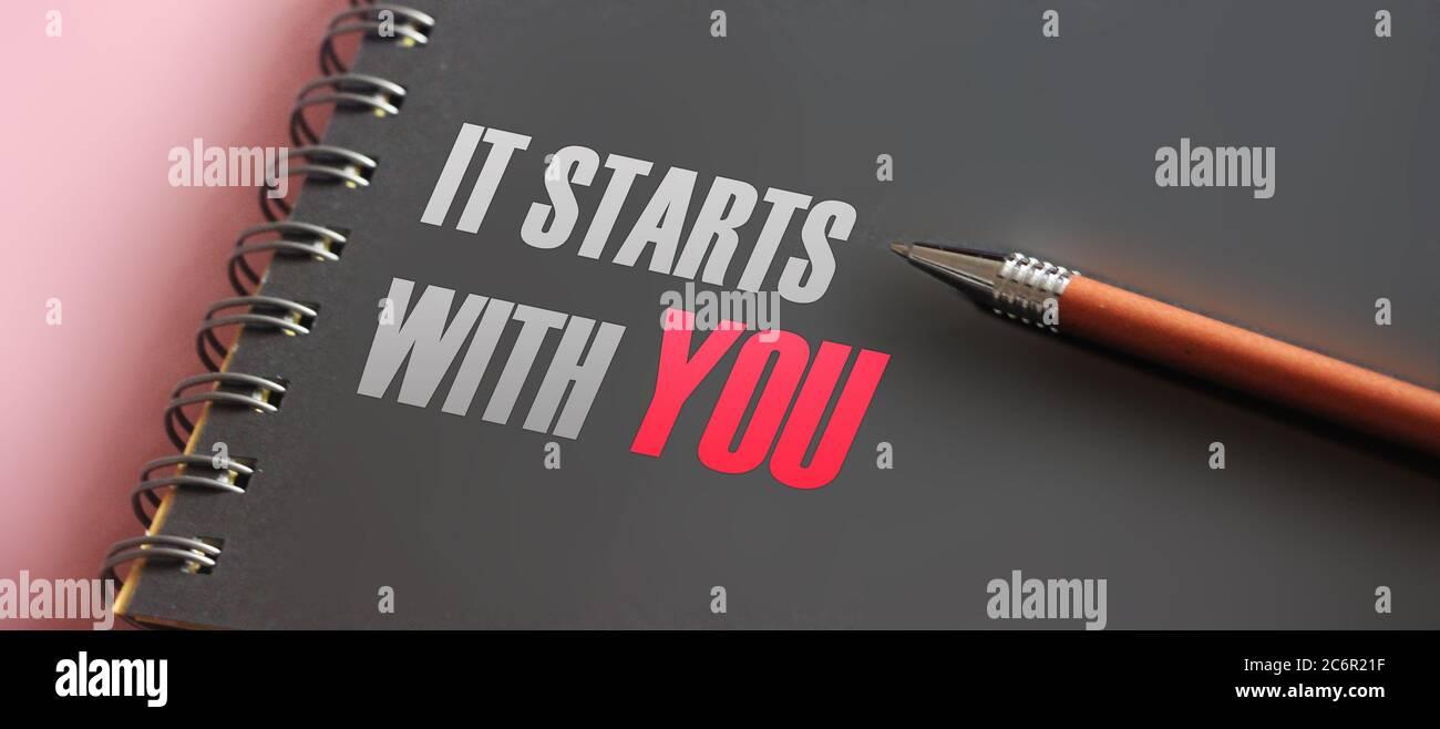 Es beginnt mit Ihnen Wörter gedruckt in Notizbuch und Stift. Motivationskonzept Stockfoto